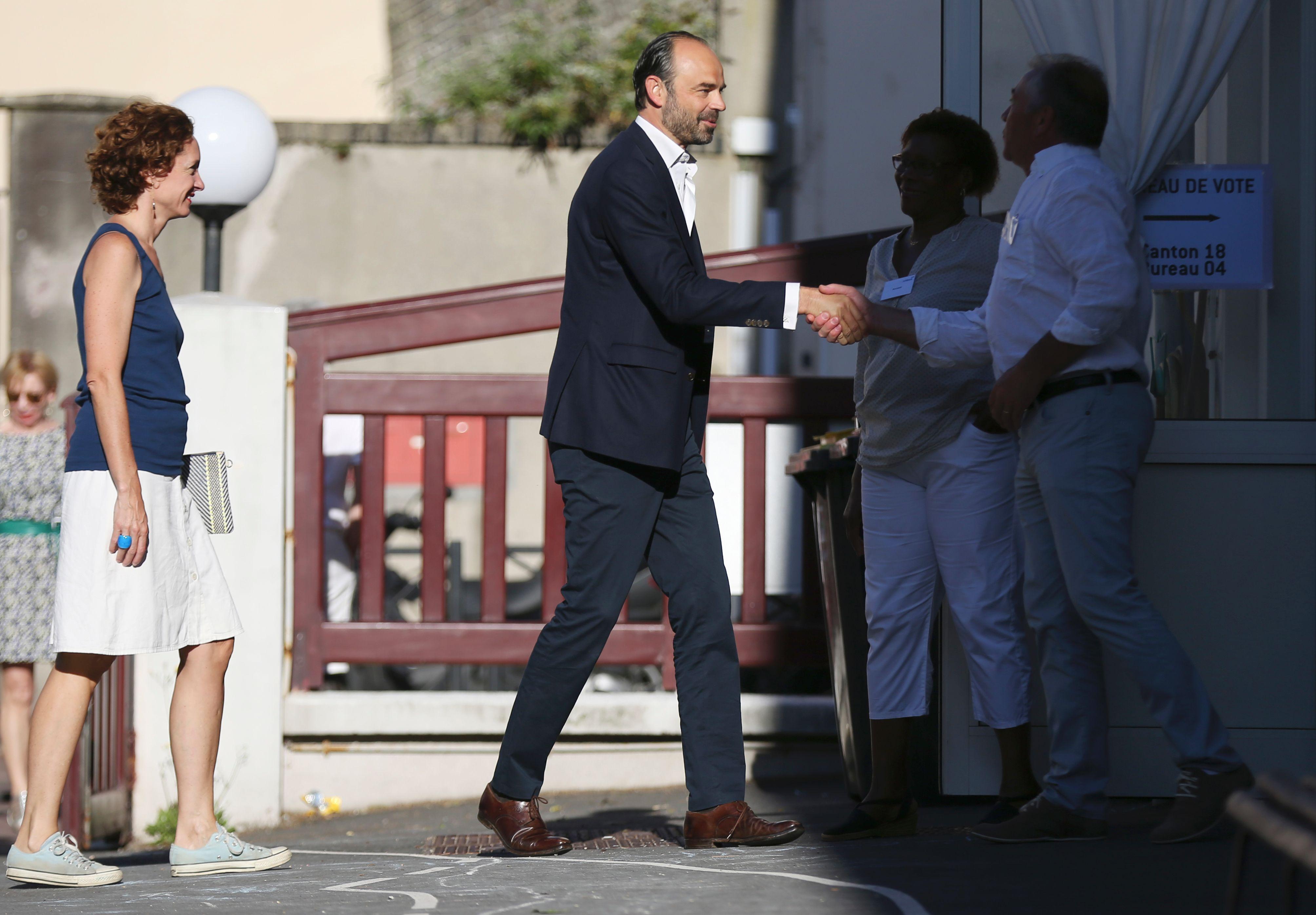 رئيس وزراء فرنسا يصافح المشرفين على الانتخابات التشريعية