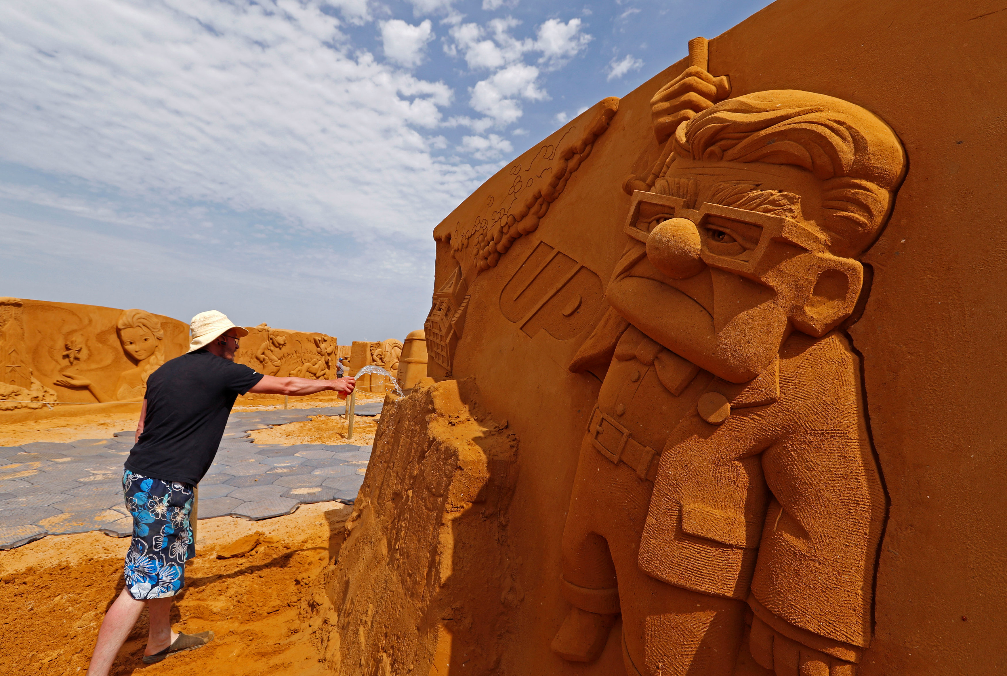 نحات يقوم بنحت تمثال رملى