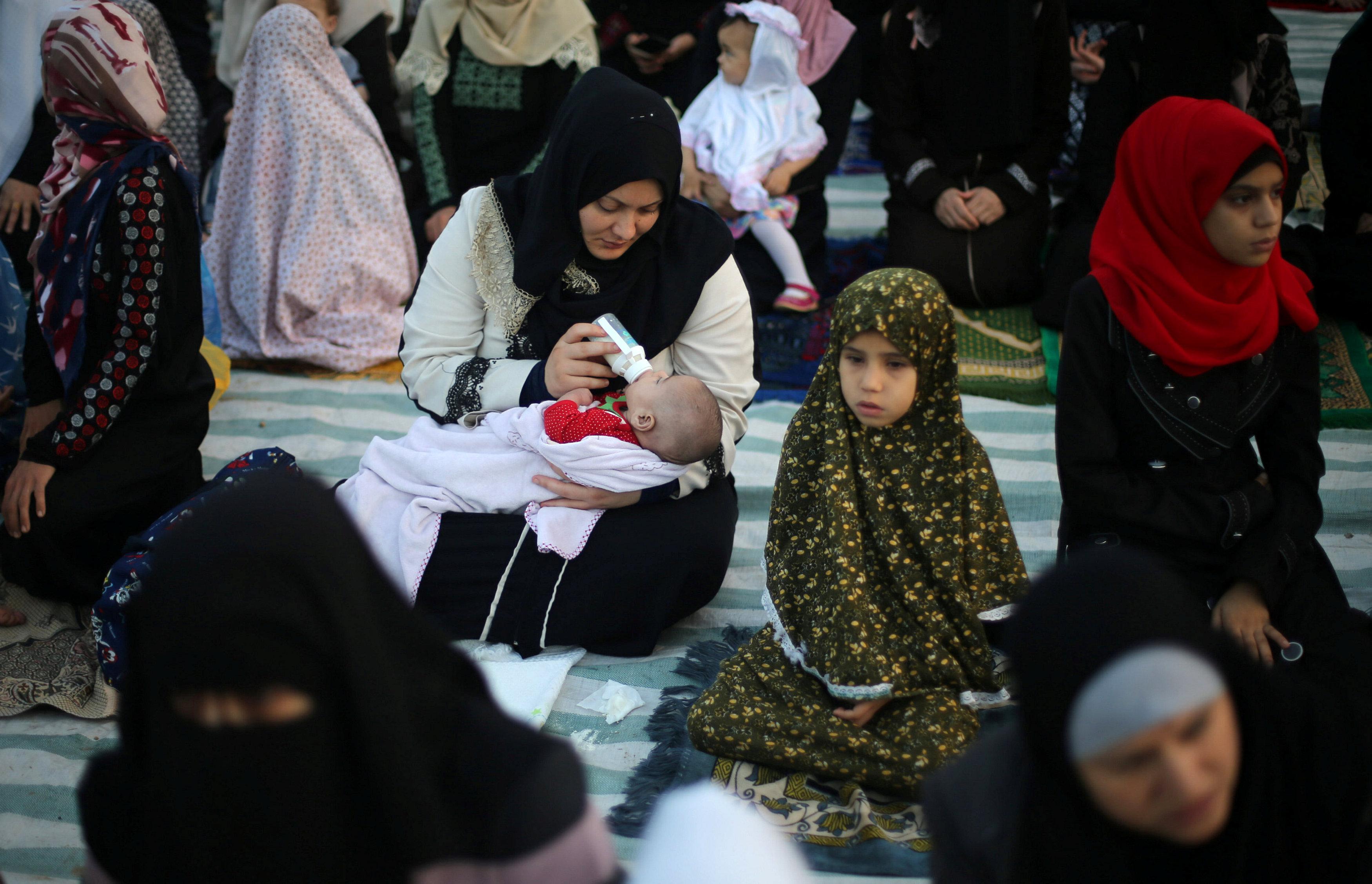 امرأة ترضع ابنها خلال صلاة عيد الفطر