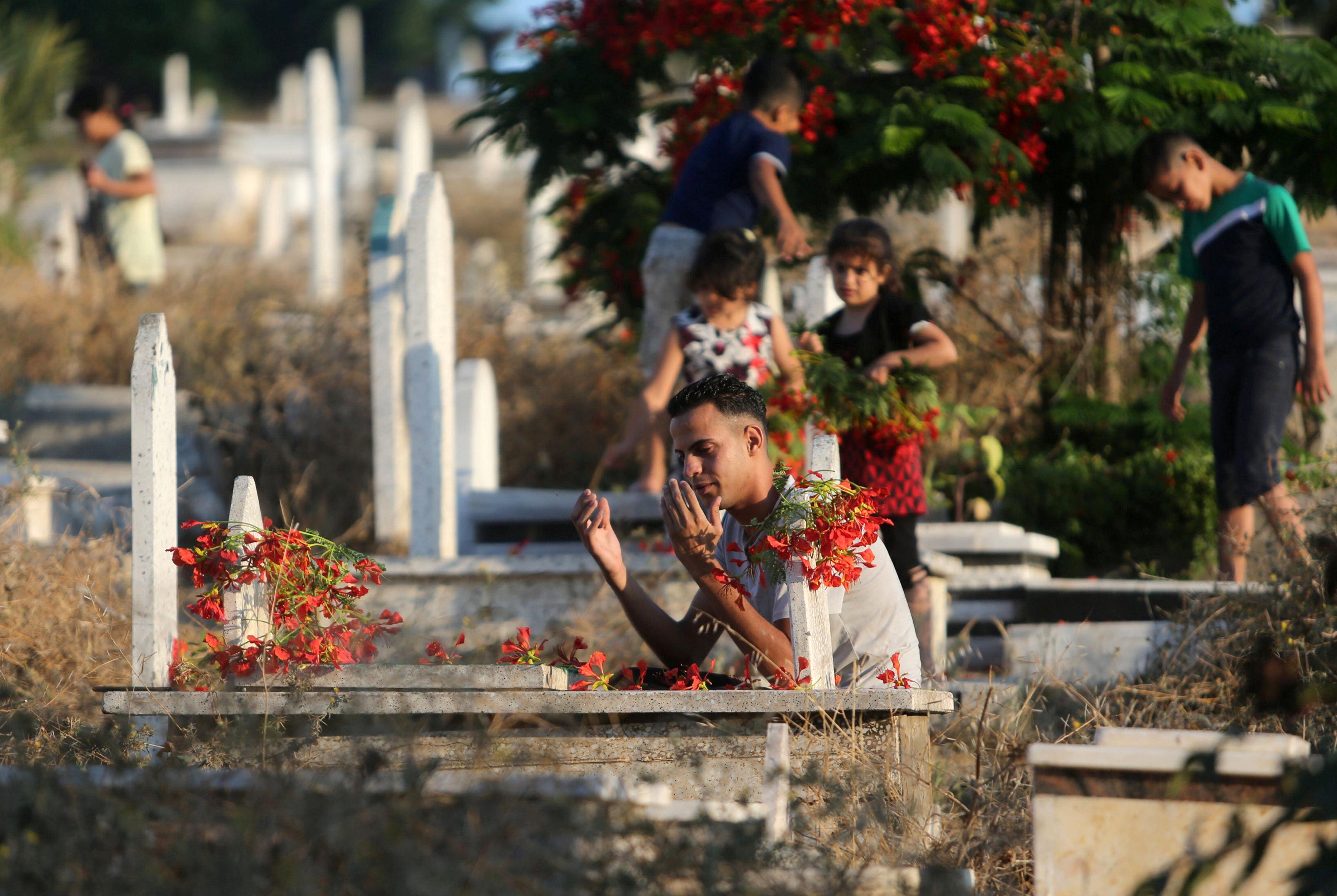 شاب فلسطينى يصلى بجوار القبر