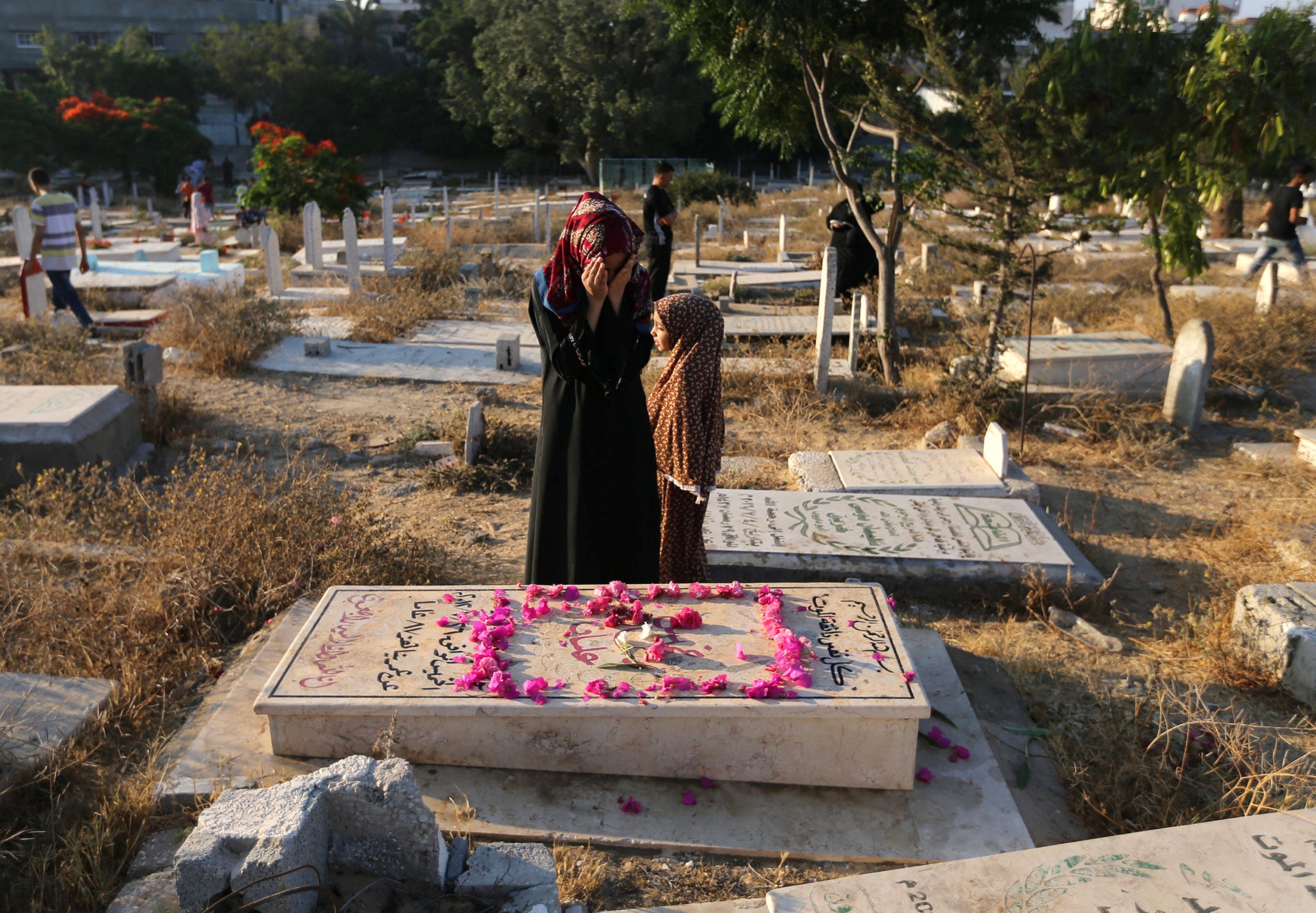 فلسطينية تصلى بجانب القبر