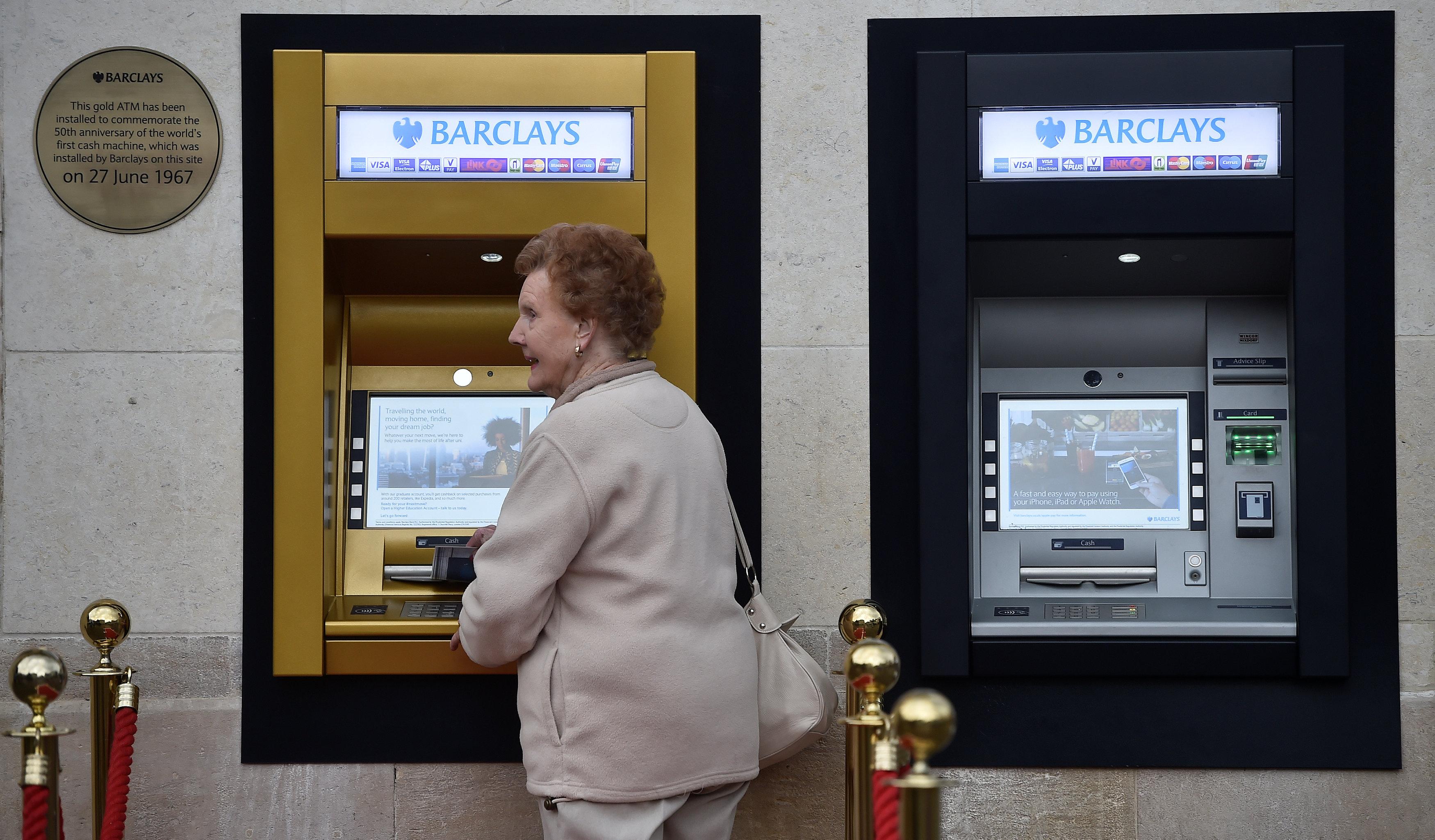 سيدة قرب أول ماكينة صرف آلى فى العالم باللون الذهبى