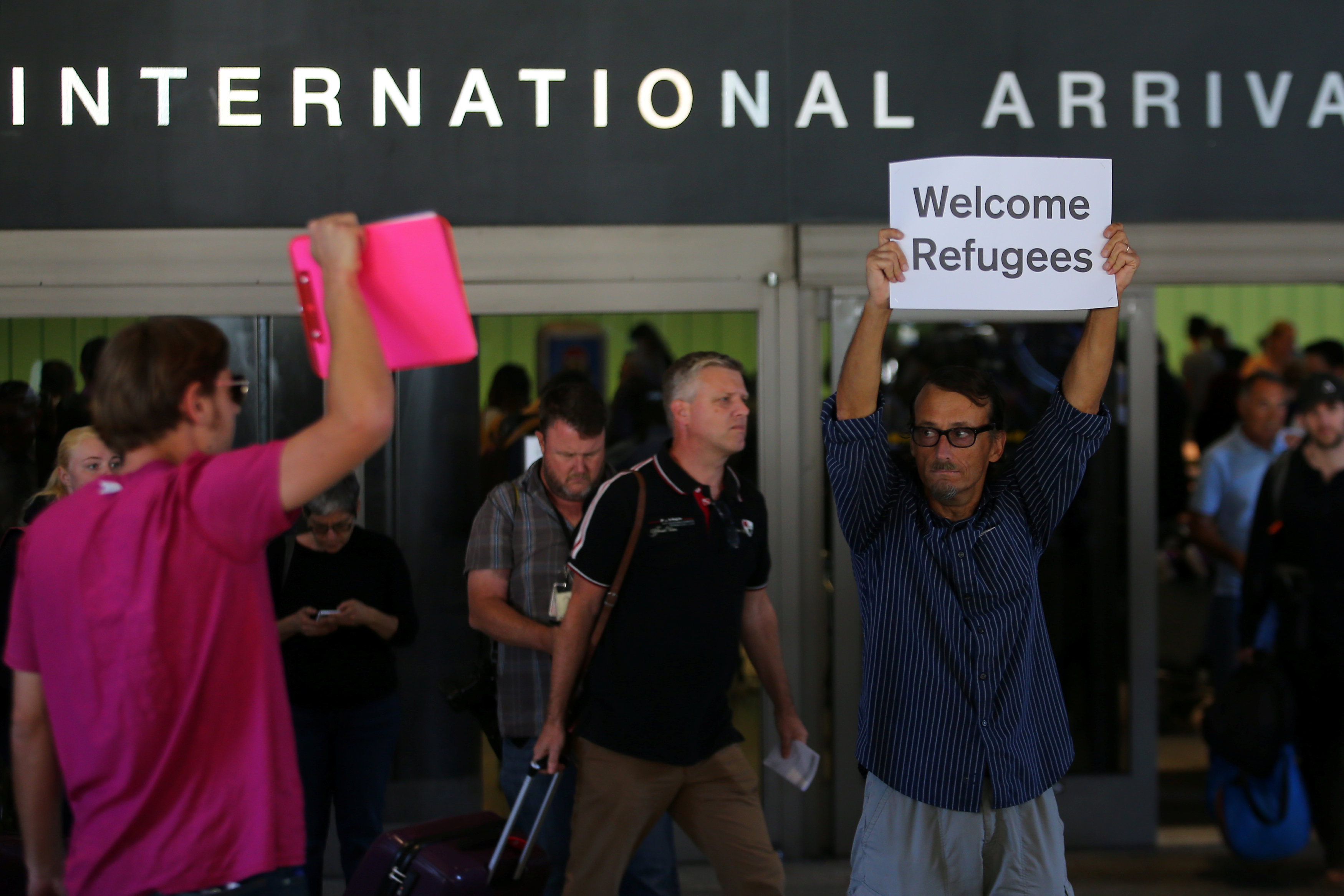 المهندس جون ويدر يرفع لافتة ترحب باللاجئين
