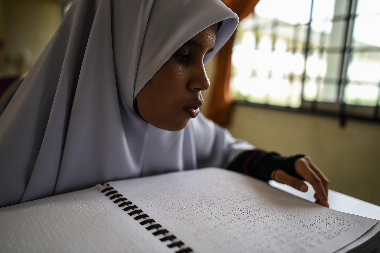 محاولة فتاة ماليزية التغلب على اعاقة البصر لقرأة القرآن فى رمضان