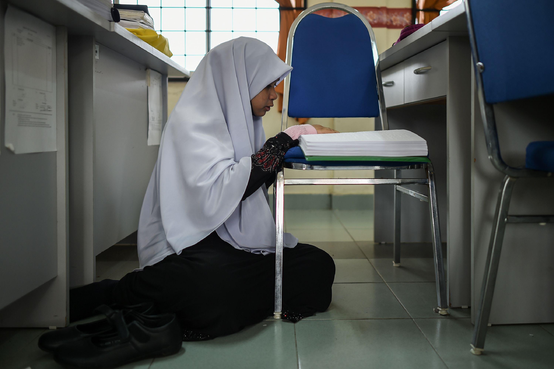 فتاه تجلس على الارض وأمامها المصحف المكتوب بطريقة برايل
