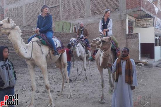 السياح يستمتعون بمشاهد النيل والجبال والمعابد على ظهر الدواب