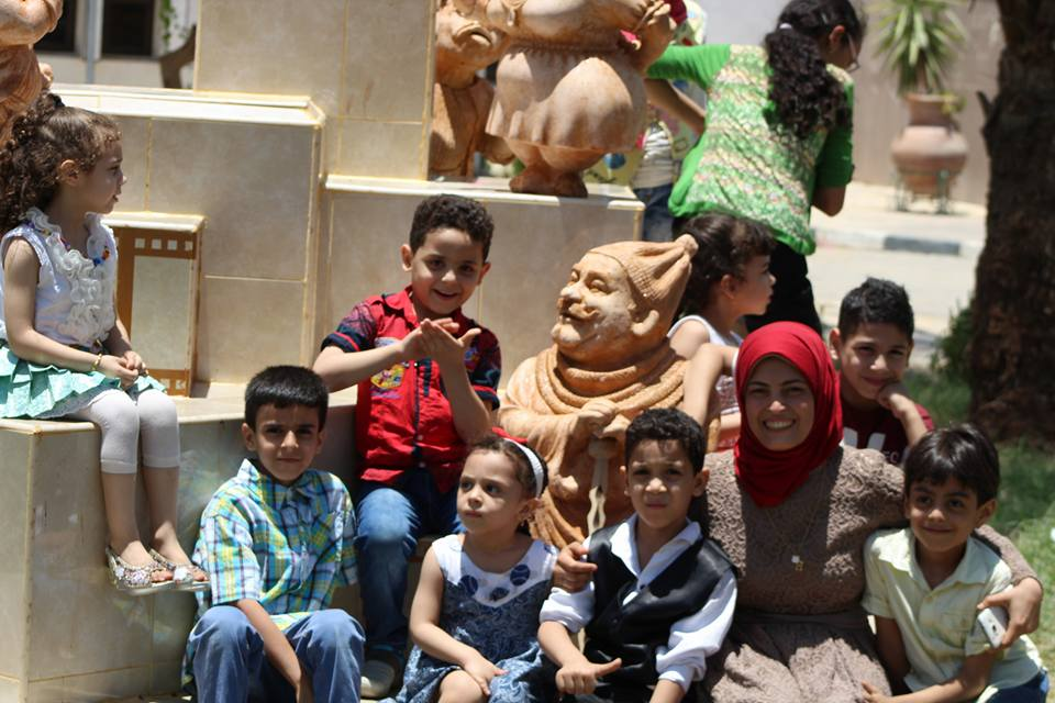 مى والأطفال يجلسون بين التماثيل