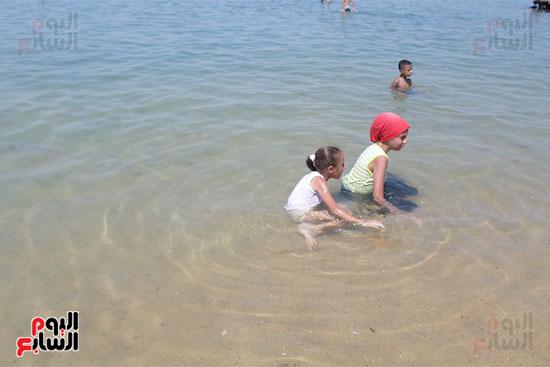 شقيقتان تستمعان بمياه الشاطئ