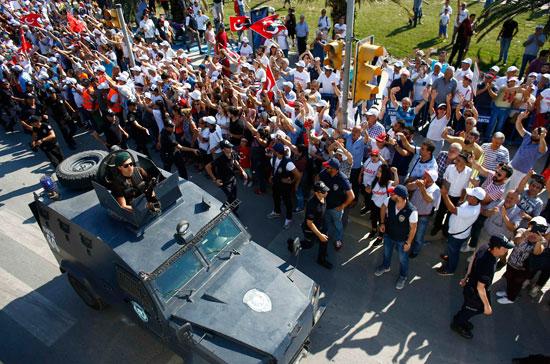 سيارة شرطة قرب المتظاهرين