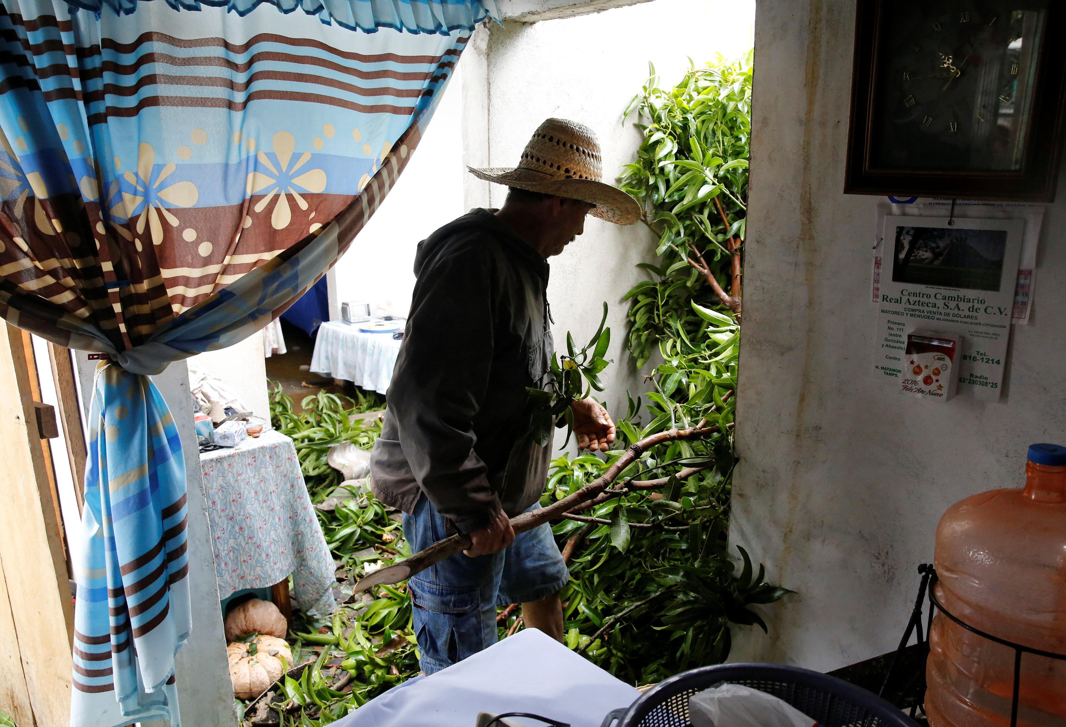 رجل ينظف منزله من آثار العاصفة