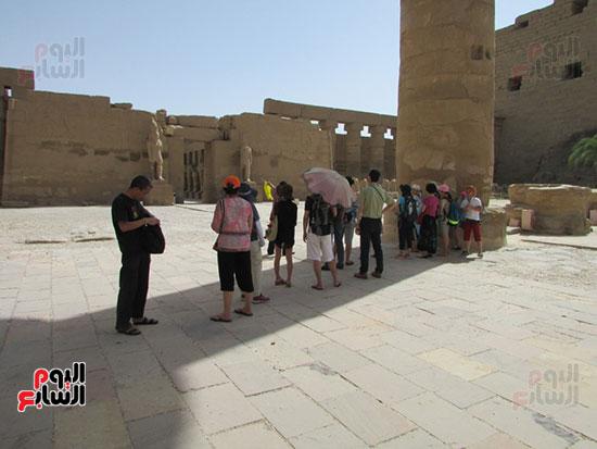 السائحون يستمعون لشرح المرشدين عن تاريخ الفراعنة