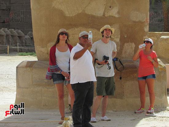 السياح يستمعون لشرح المرشد بمعبد الكرنك