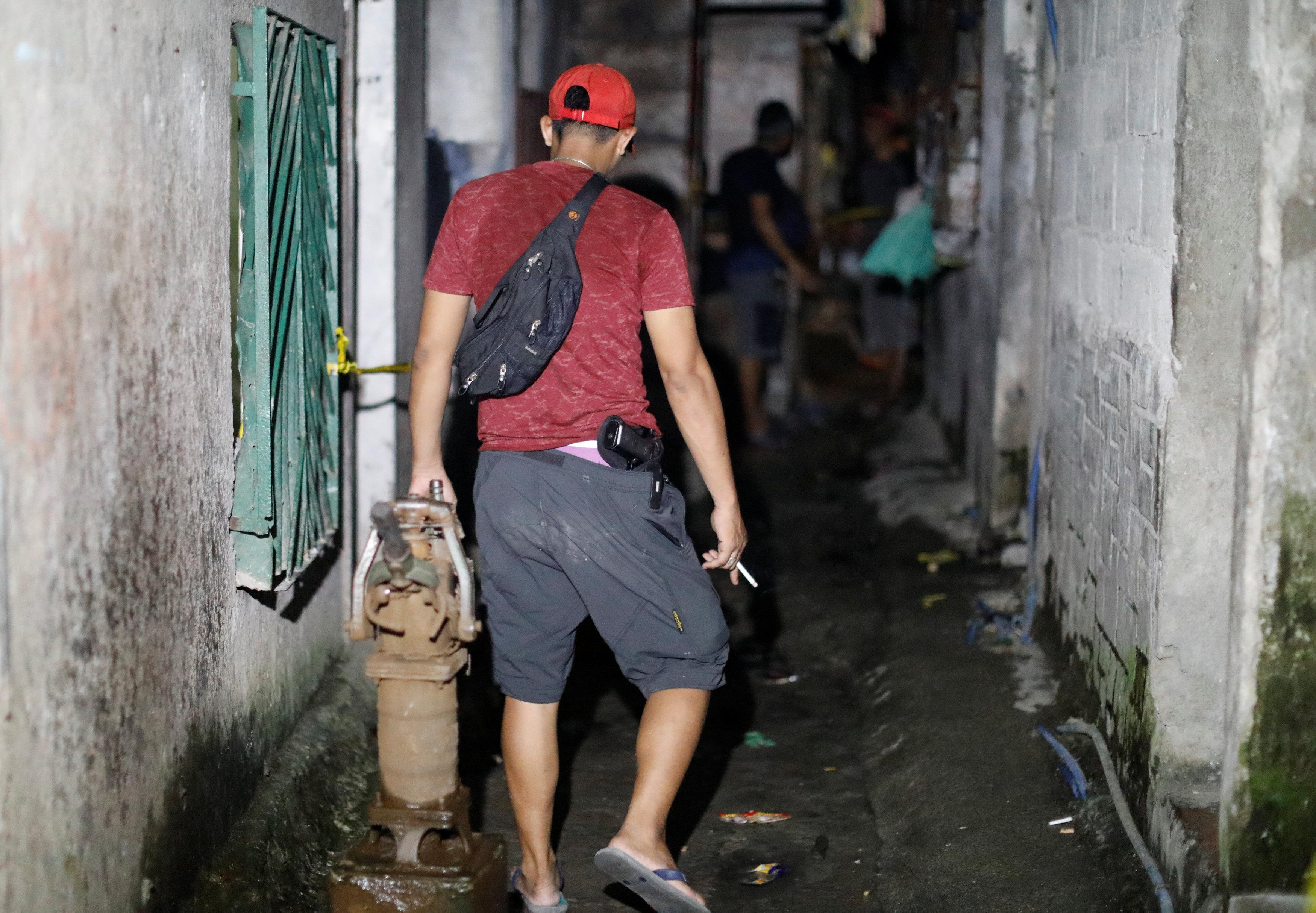 أحد أفراد الشرطة الفلبينية بزى مدنى يسير وسط البيت