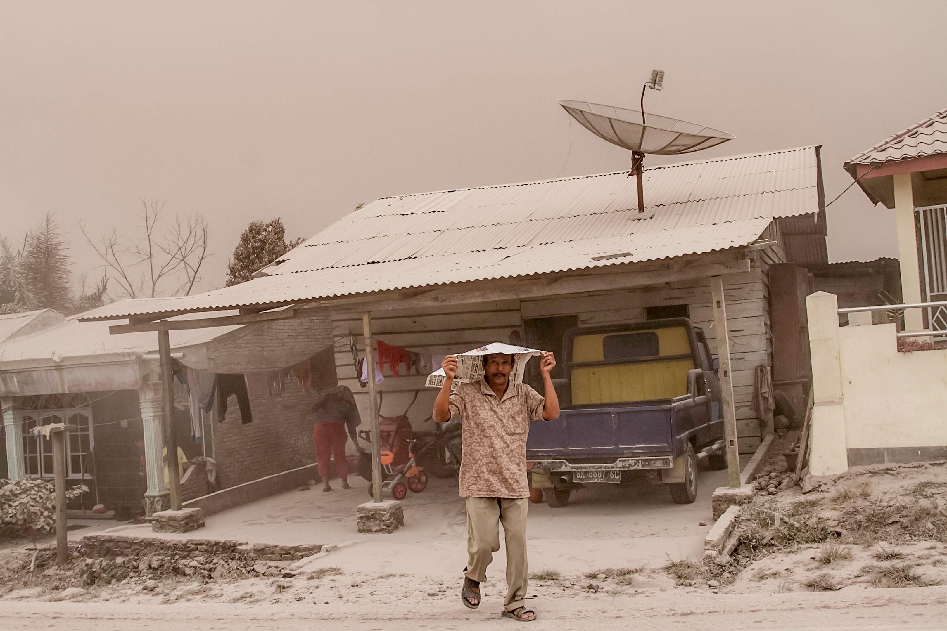 مواطن يغطى نفسه من الرماد البركانى