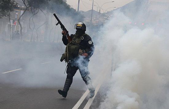 أحد عناصر الشرطة يطلق الغاز المسيل للدموع