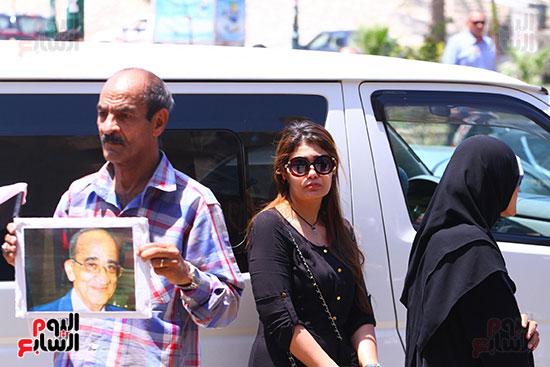 مواطن يحمل صورة على السمان فى الجنازة