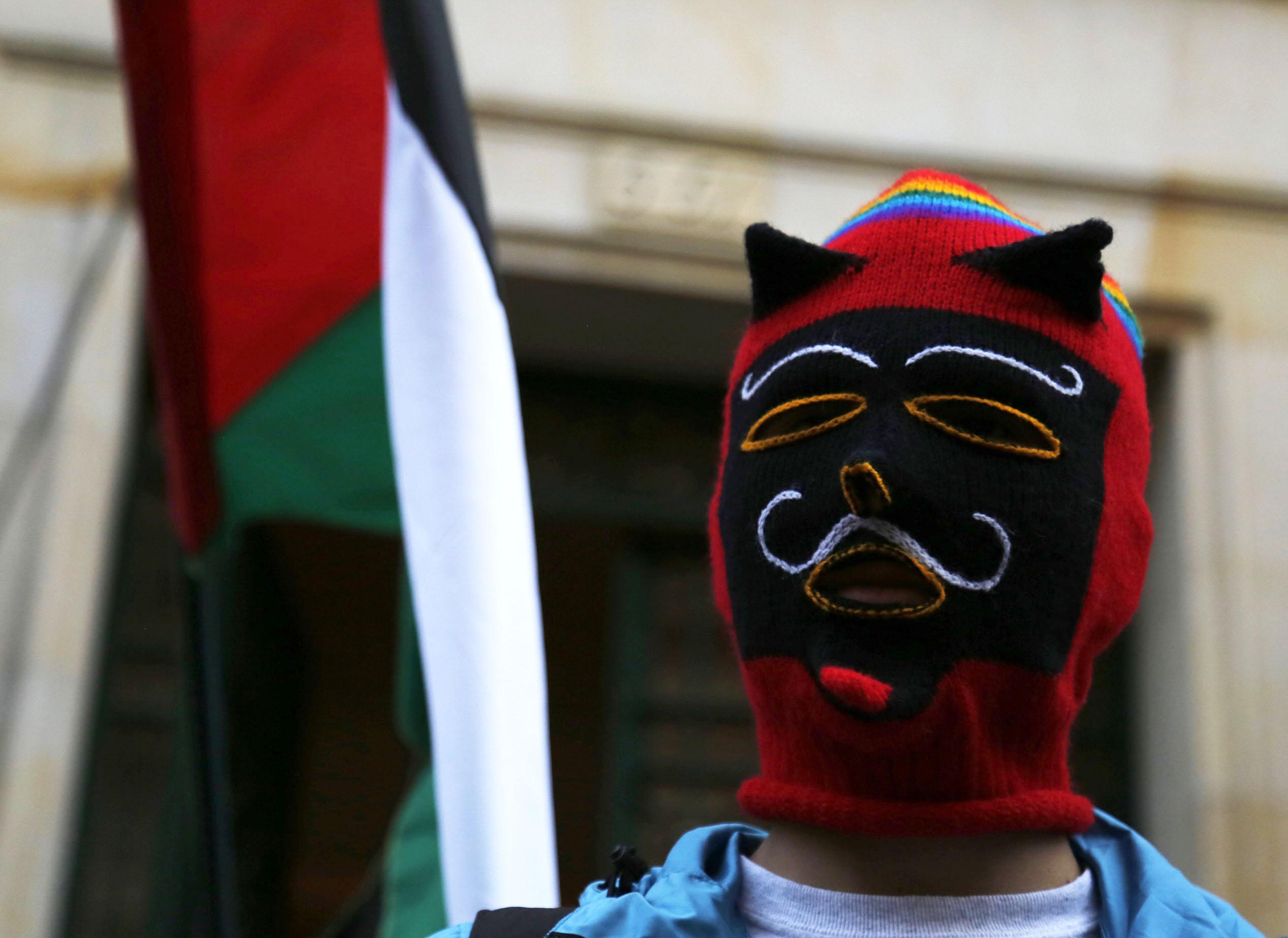 أحد المحتجين يرفع العلم الفلسطينى