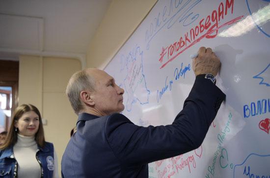 بوتين يوقع داخل مقر الحملة