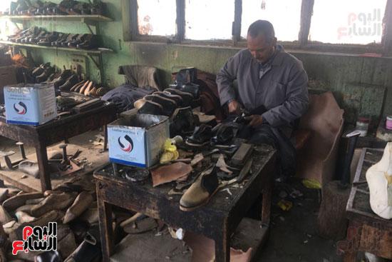 احد العمال يقوم بصناعة حذاء طبي