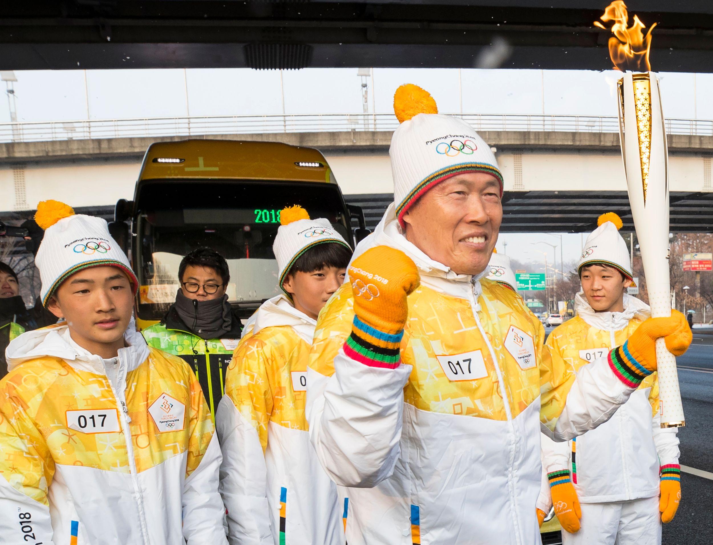 أحد الرياضيين فى كوريا الجنوبية يحمل الشعلة الأولمبية