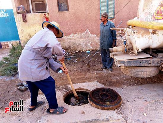 عمال الصرف الصحى يستخرجون زجاجات