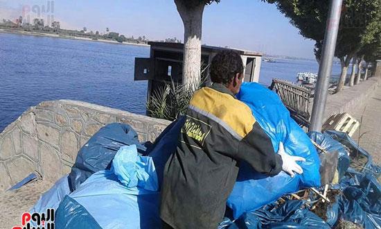 العمال خلال رفع المخلفات المرفوعة من النيل