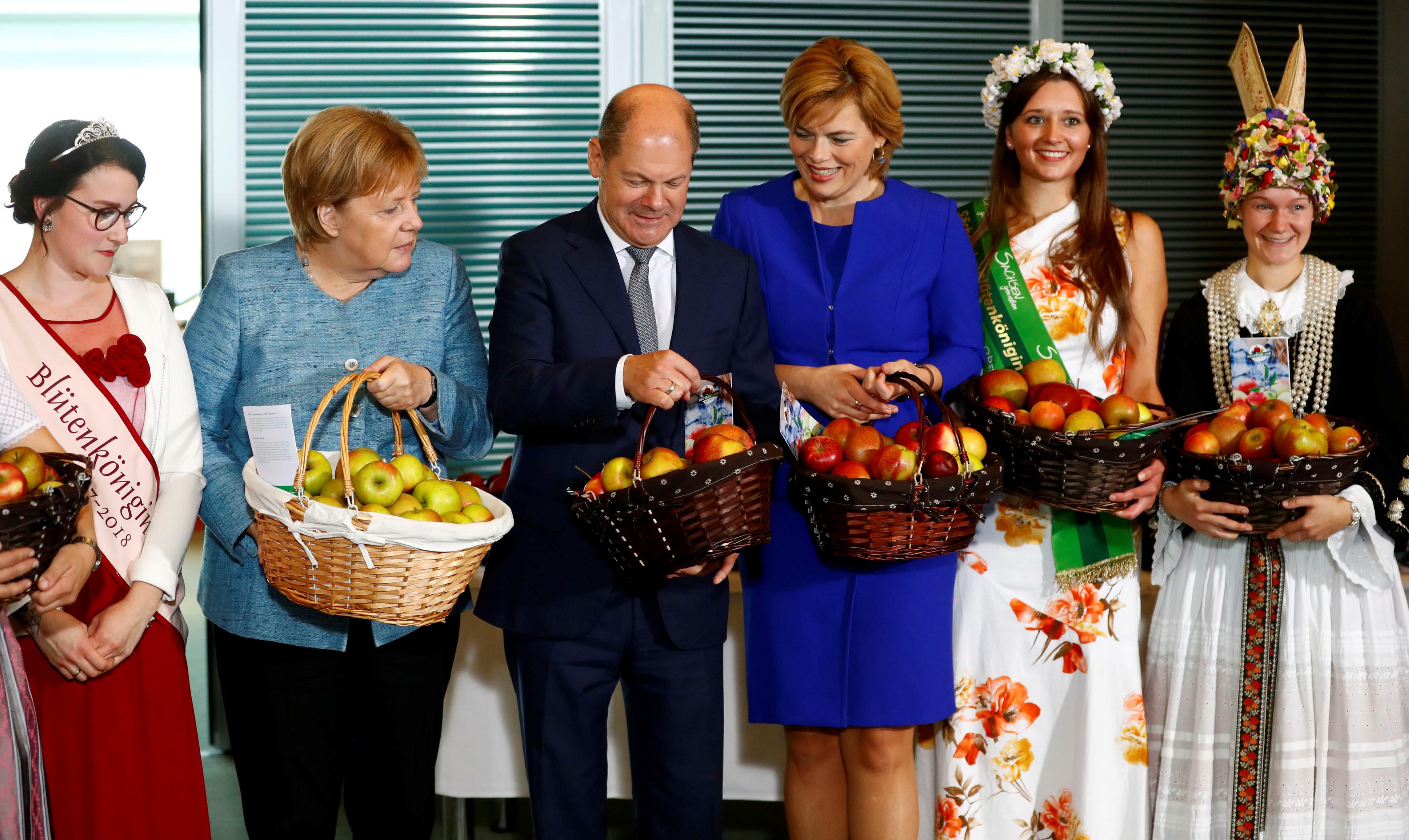 ميركل وعدد من وزرائها يحملون التفاح