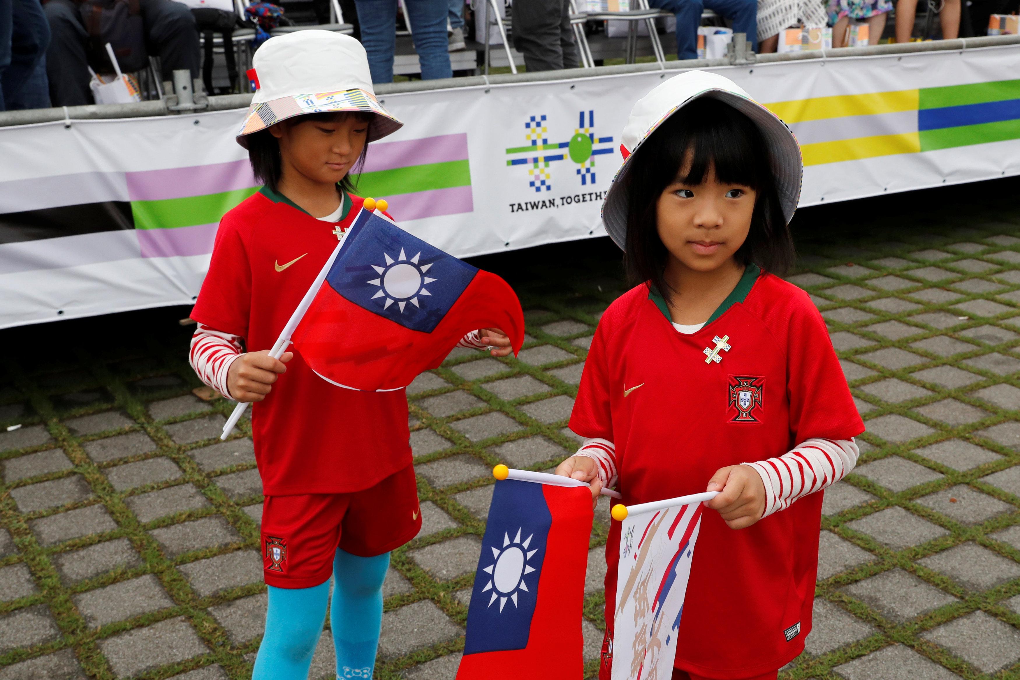 طفلان يرتديان أزياء بألوان علم تايوان ويحملان أعلامها
