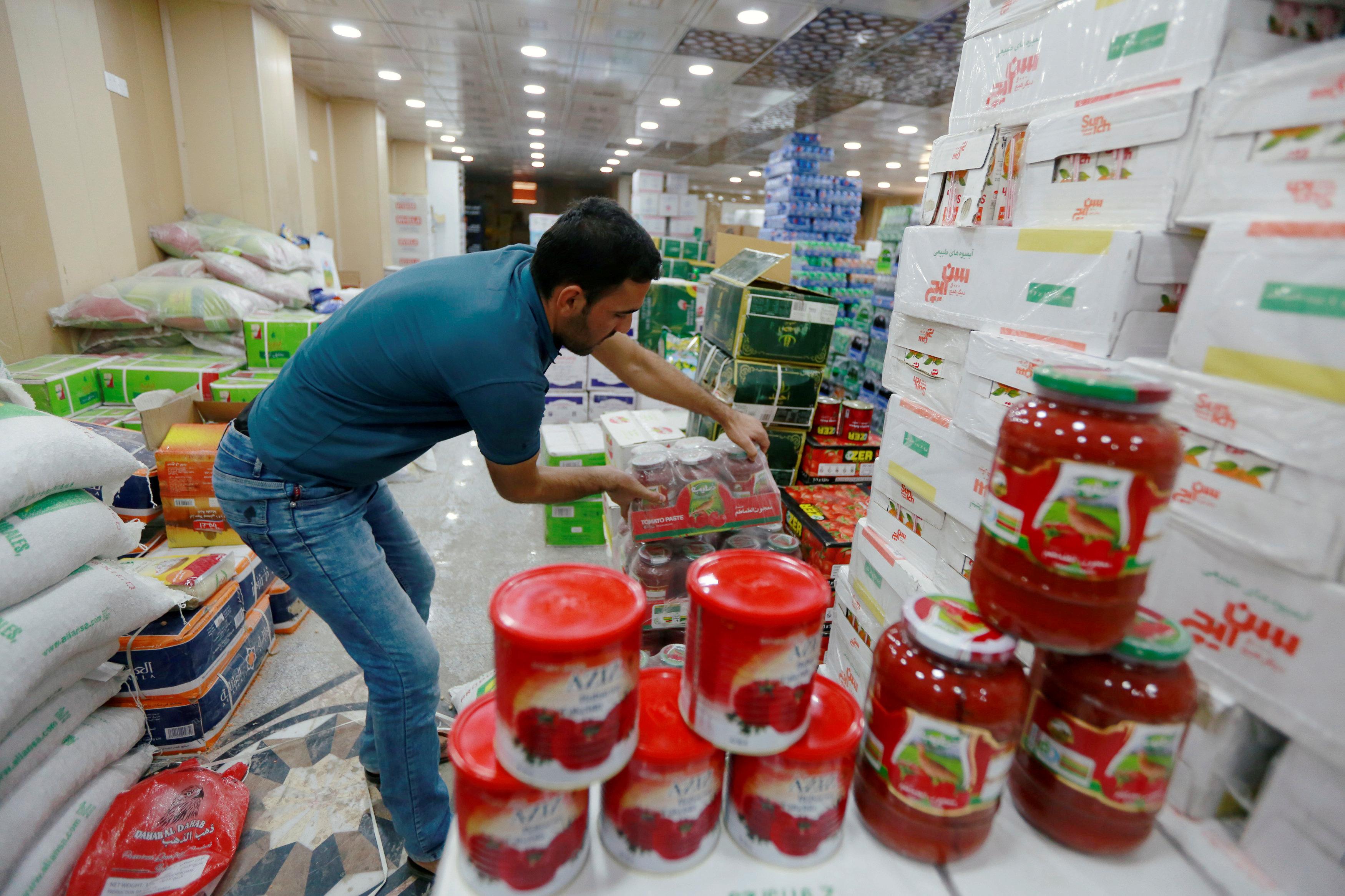 أحد العمال تقوم بترتيب منتجات الطماطم الإيرانية