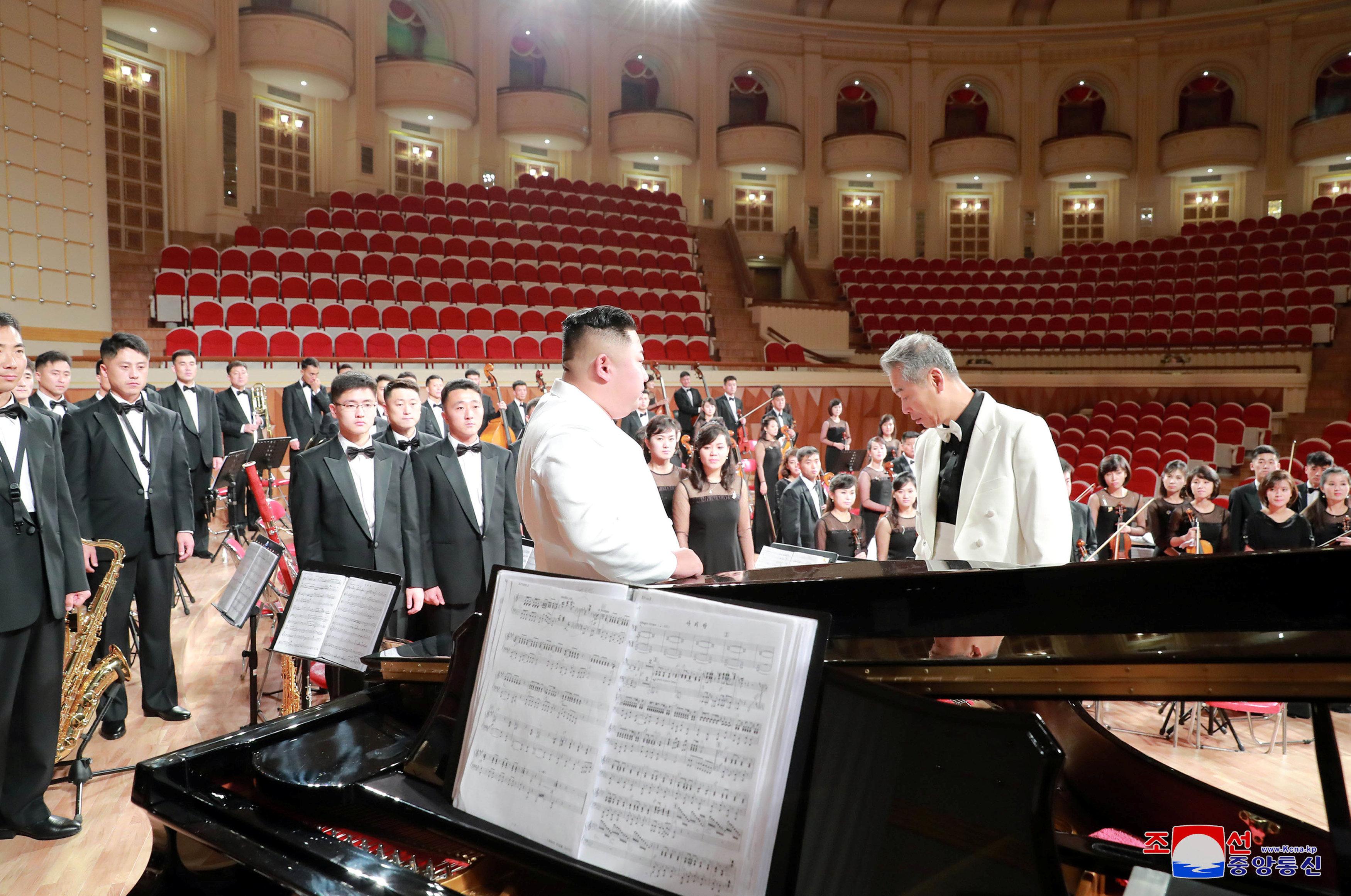 كيم فى حديث مع قائد الأوركسترا فى مسرح بيونج يانج