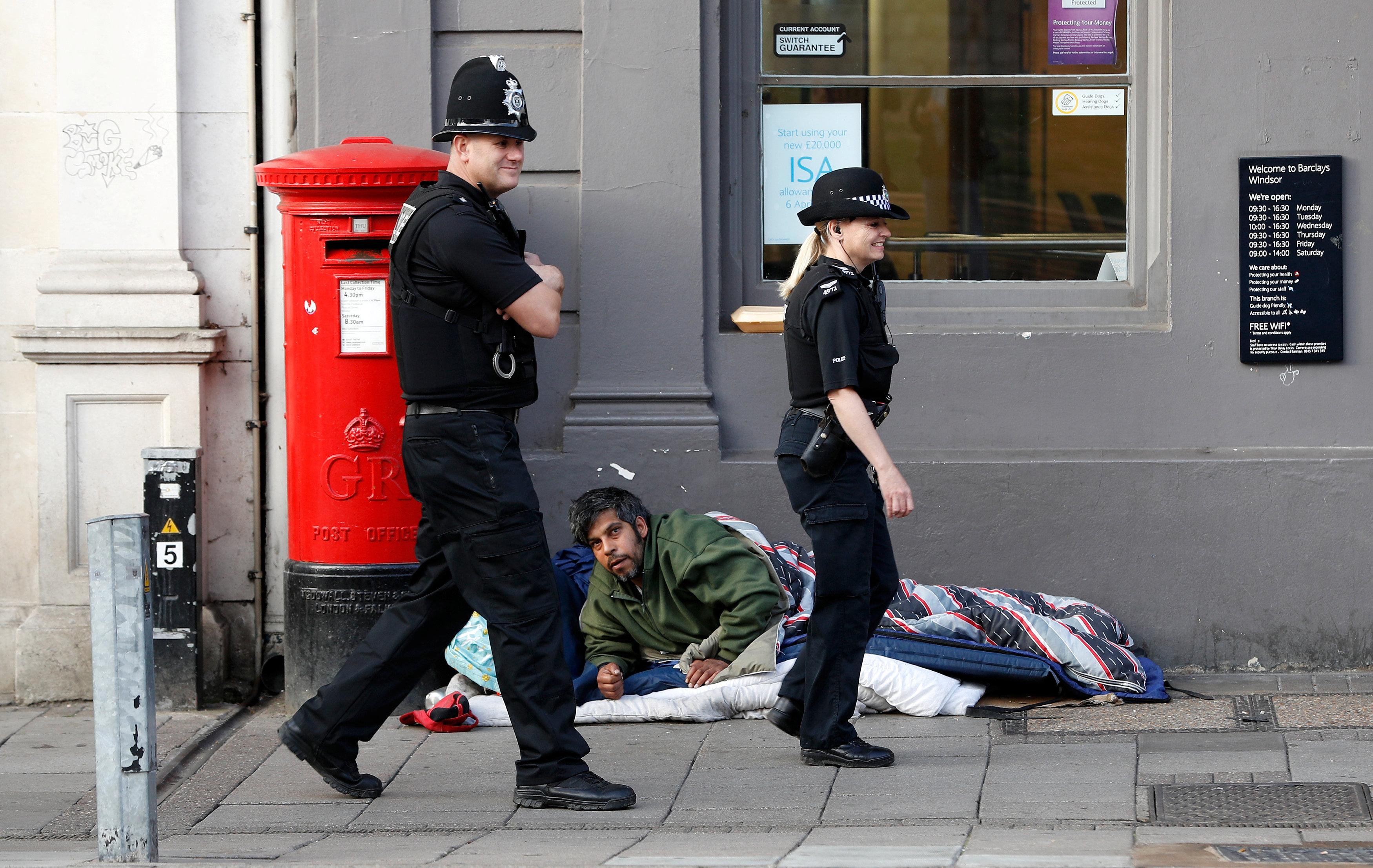 الشرطة البريطانية تمر بجوار أحد المشردين