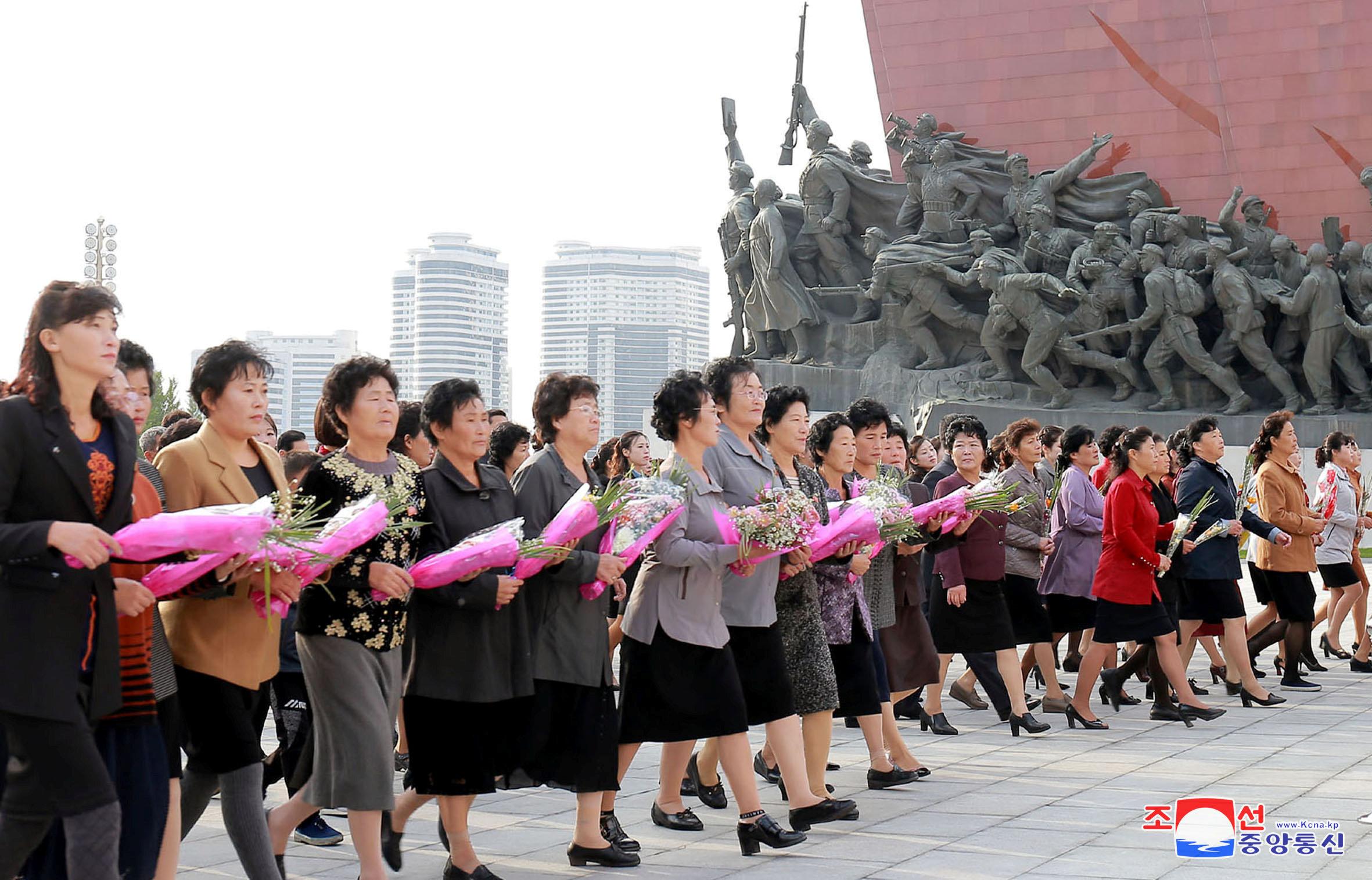 مواطنات كوريا الشمالية يحملون الورود أمام النصب التذكارى لمؤسس كوريا الشمالية