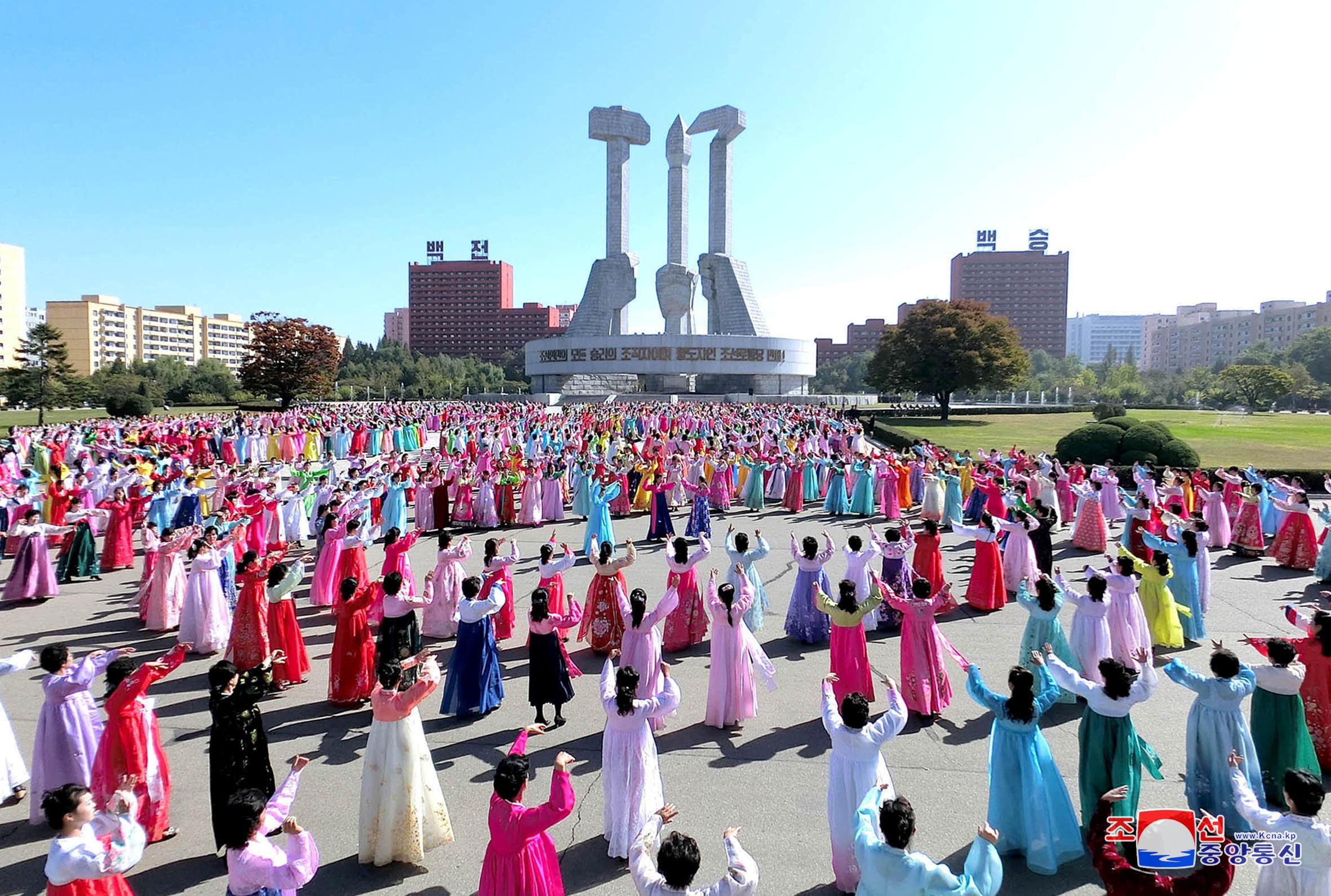 عروض راقصة أمام تمثال كبير يحمل شعار الحزب الحاكم