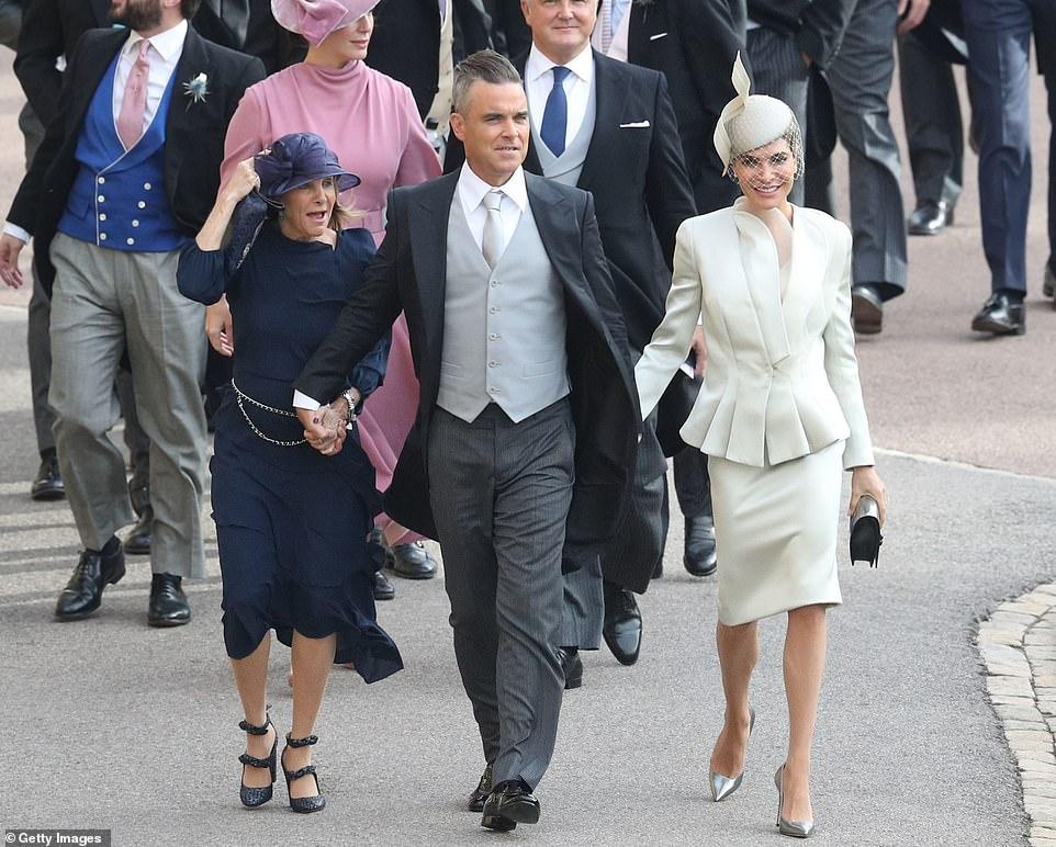روبي ويليامز مع زوجته ووالدتها التى فقدت قبعتها لاحقاً بسبب الرياح