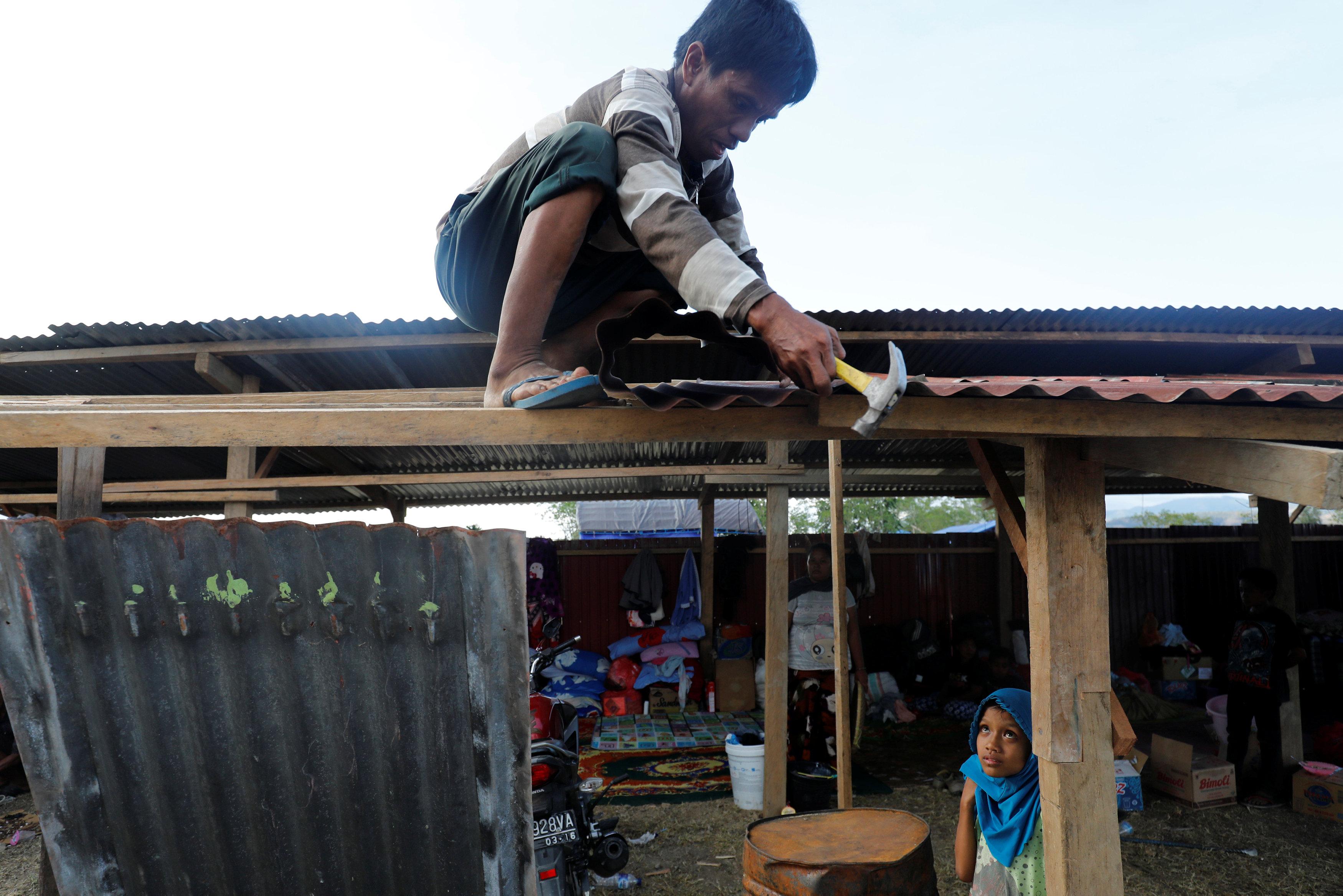 طفل إندونيسى يشارك فى عمل مخيم لأهله