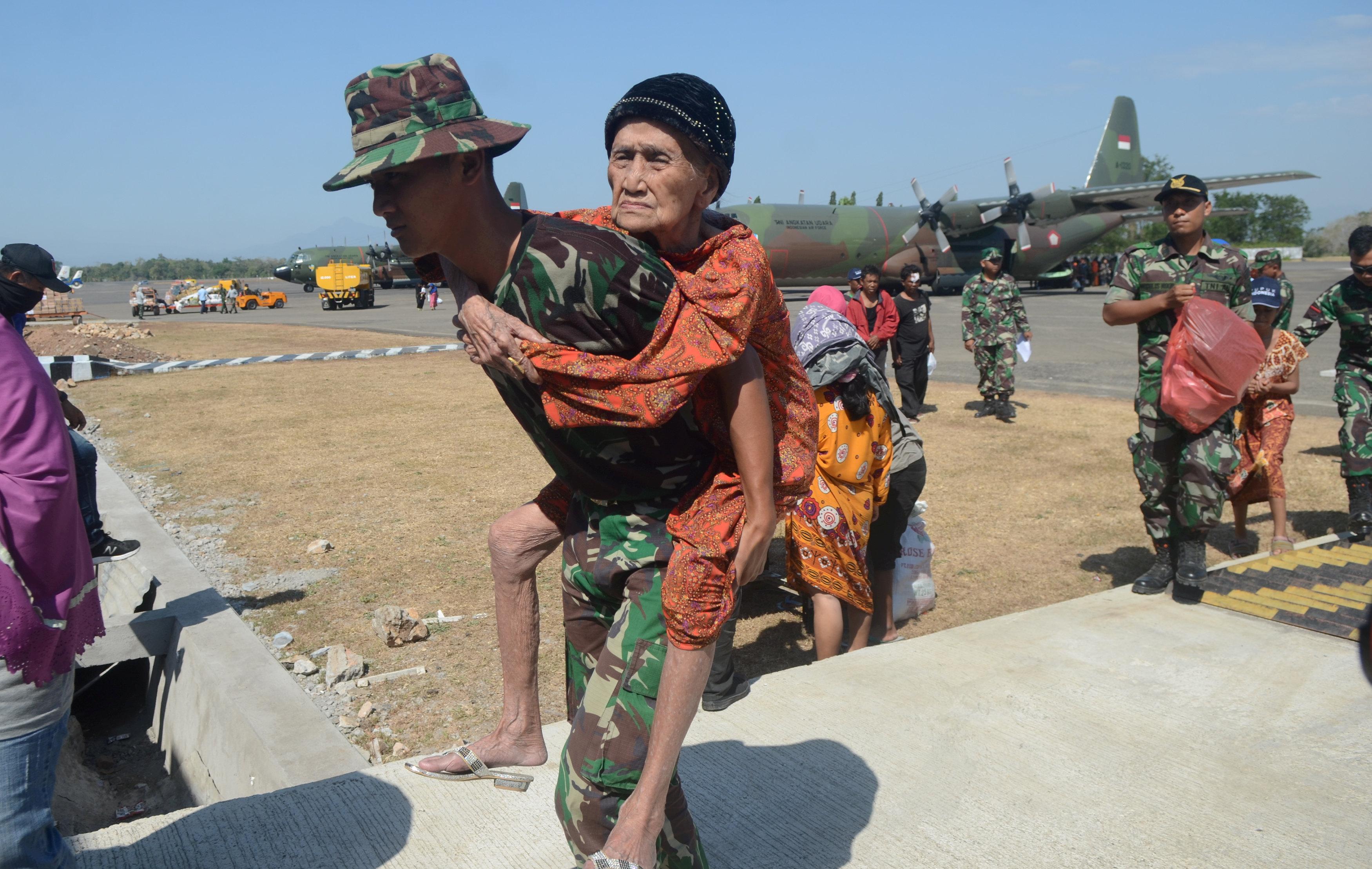 جندى إندونيسى يحمل سيدة عجوز بمناطق الزلزال