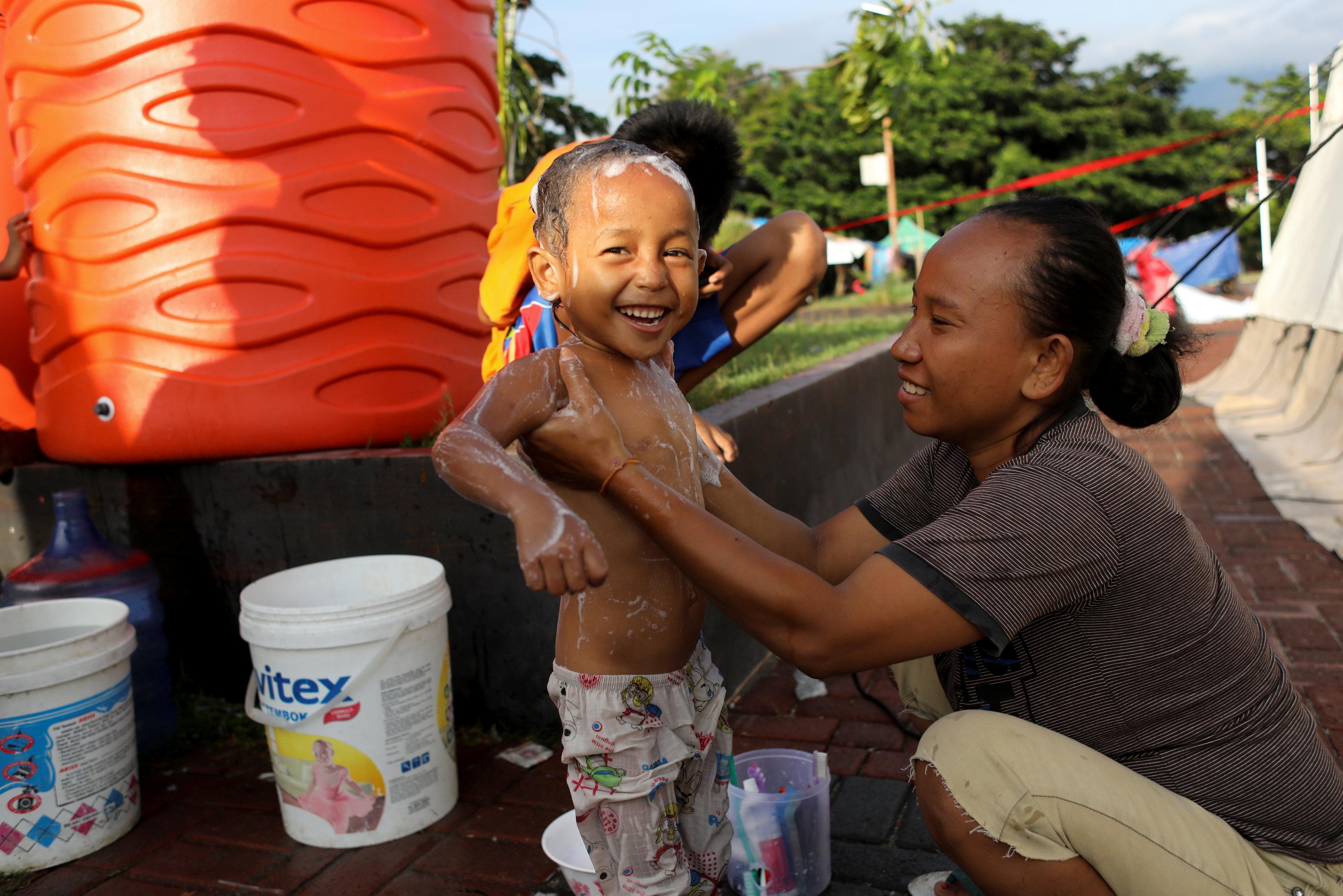 إبتسامة طفل إندونيسى بعد الاستحمام داخل إحدى المخيمات بمناطق الزلزال