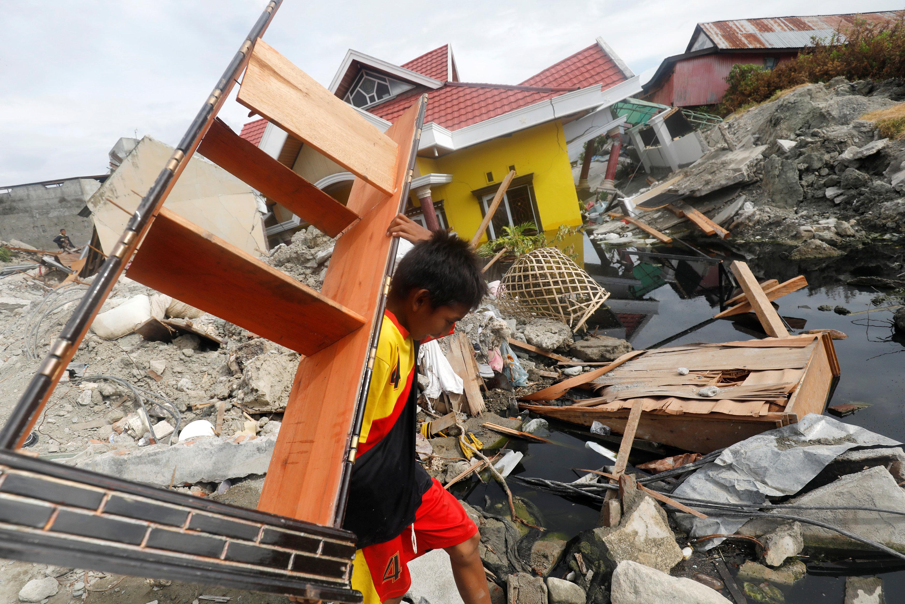 طفل إندونيسى يحمل جزء من مكتبه بعد فقدان جميع أجزاء منزله فى الزلزال