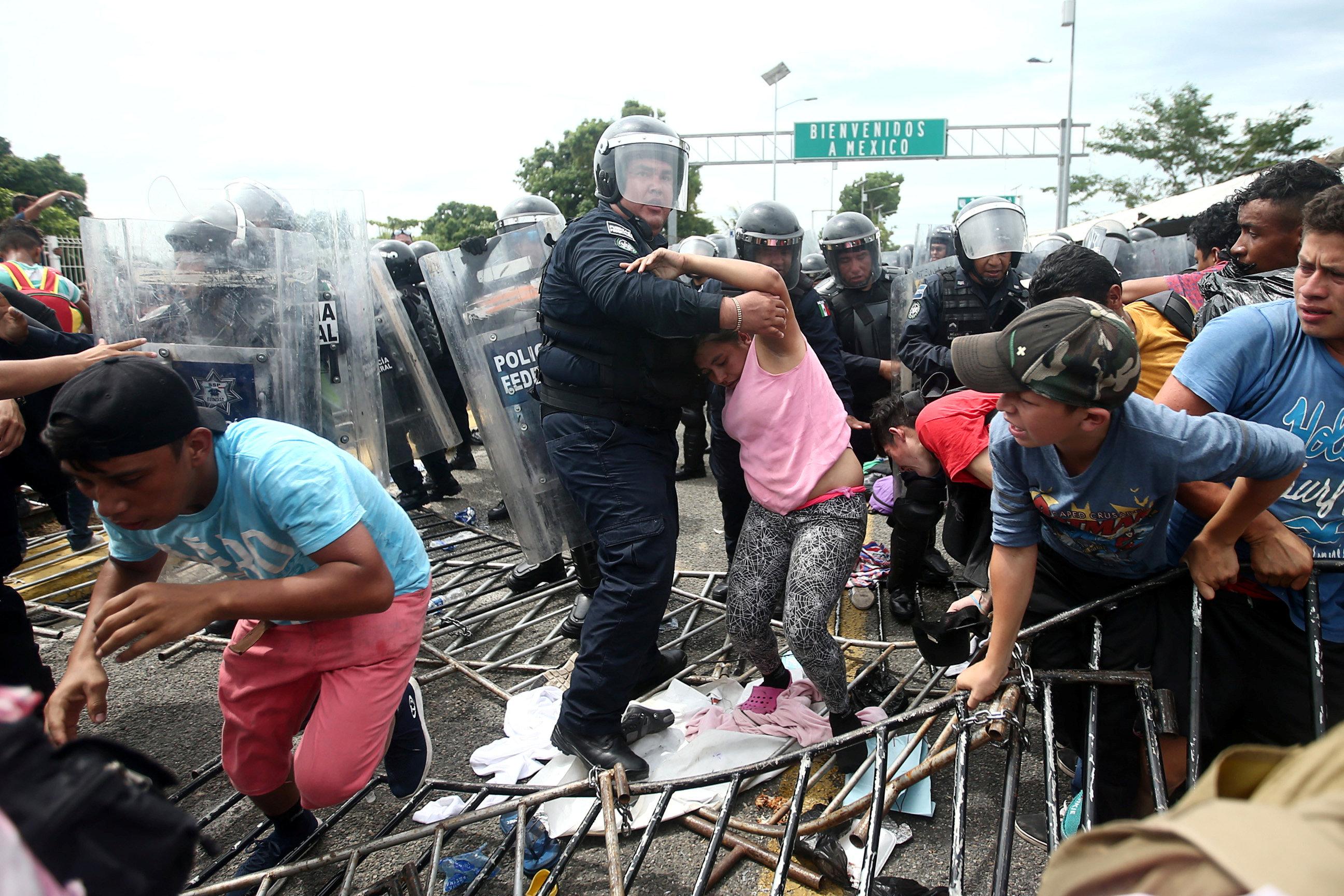 أحد عناصر الشرطة يحاول منع سيدة من العبور إلى جواتيمالا