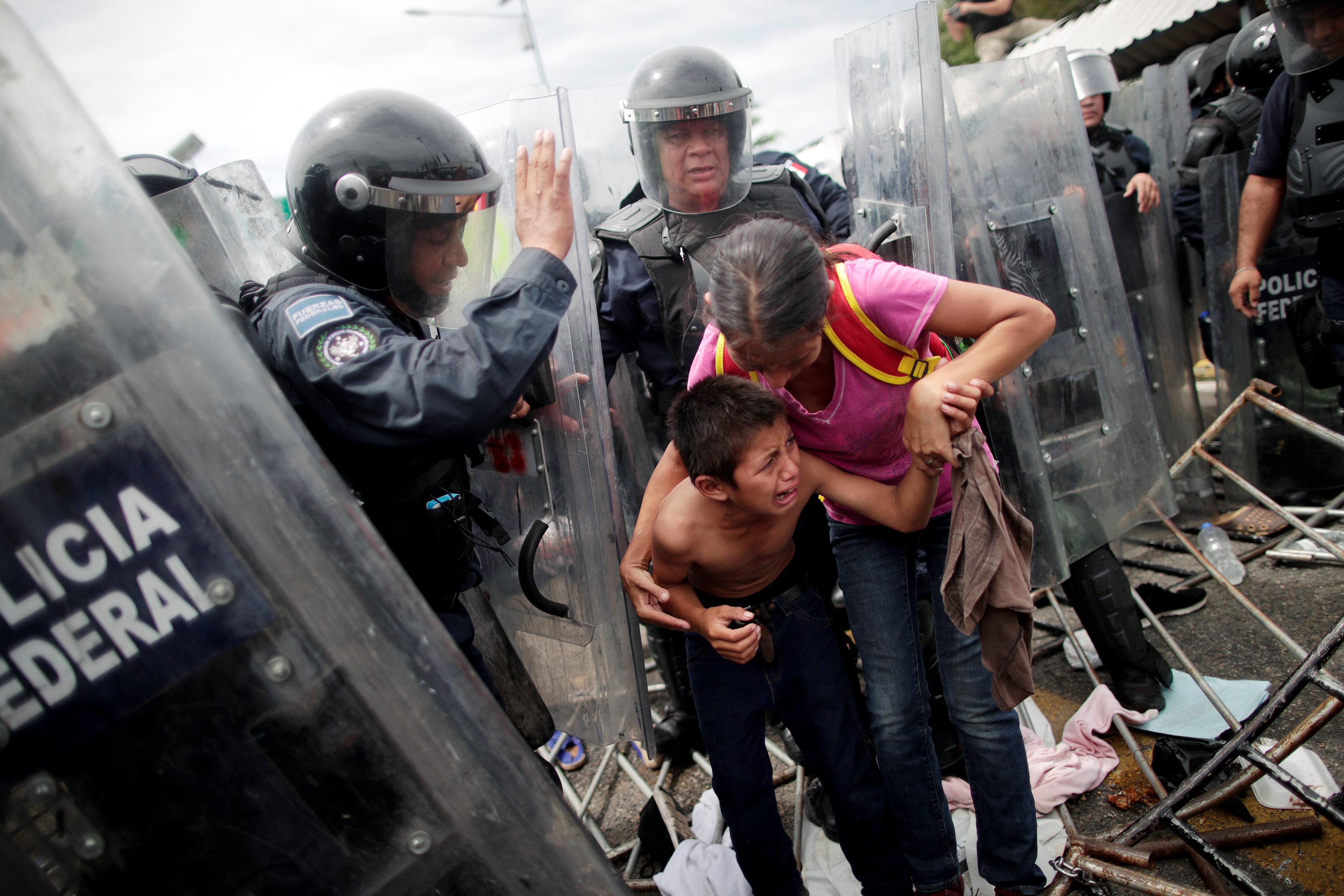سيدة تعبر بطفلها خلال الاشتباكات