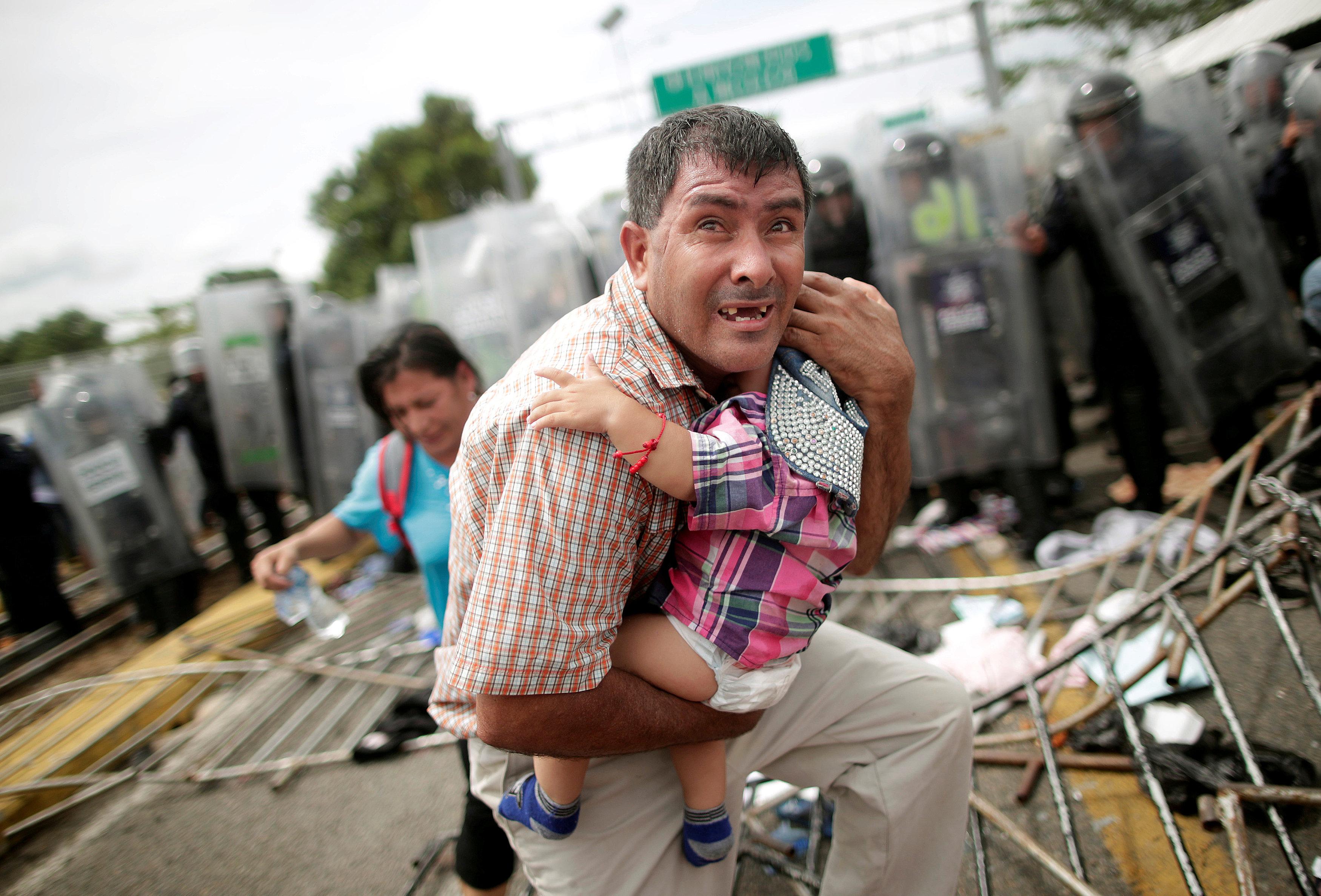 رجل يحاول حماية رضيع خلال الاشتباكات