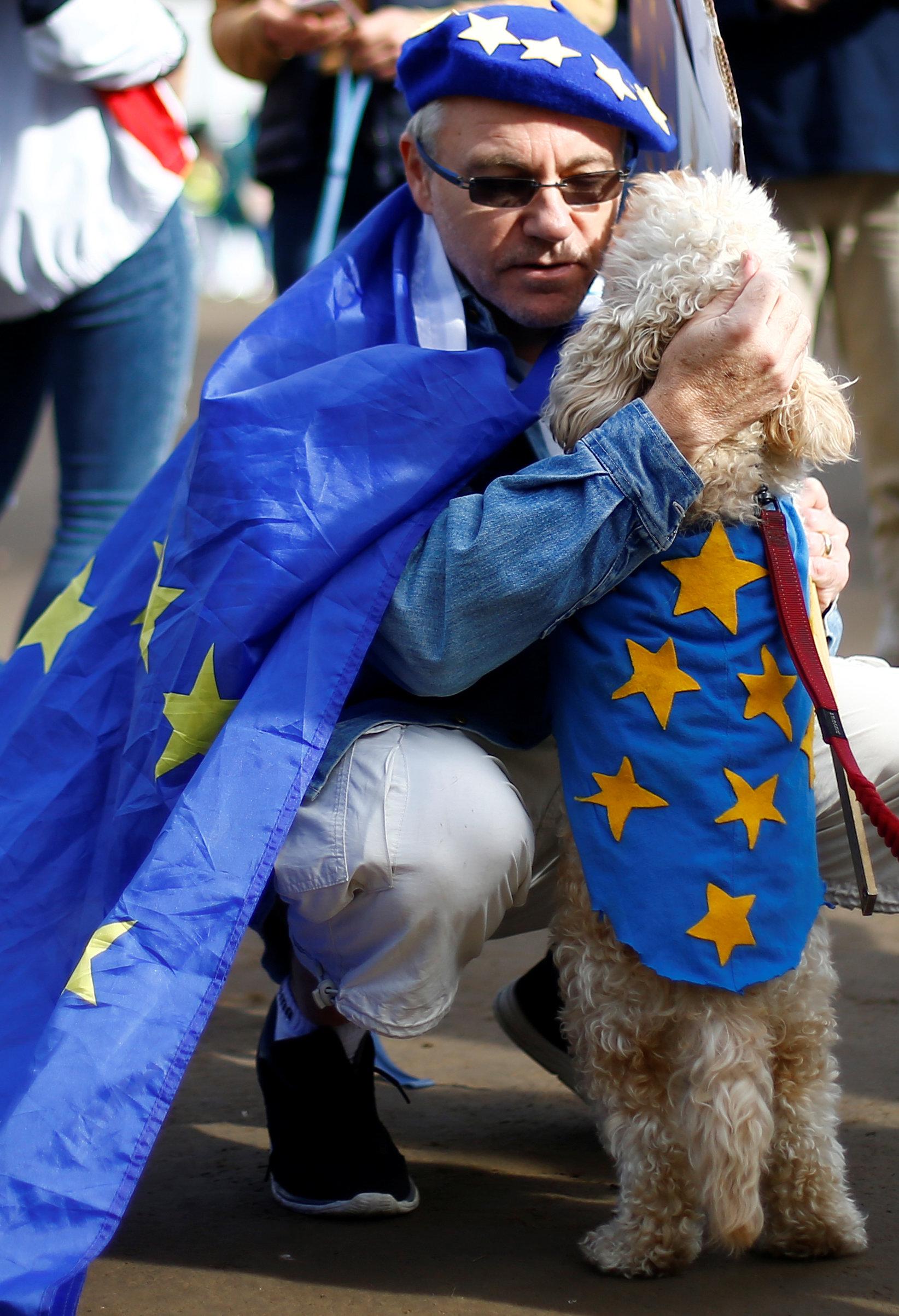 رجل يحضن كلبه خلال المسيرة