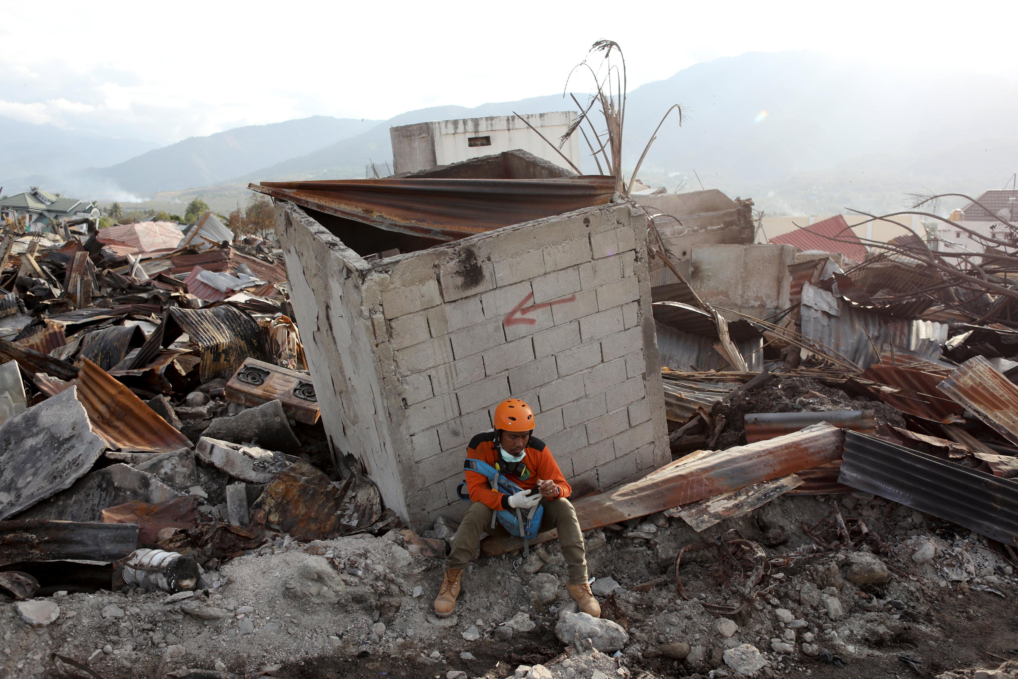 مواطن إندونيسى يجلس وسط الدمار