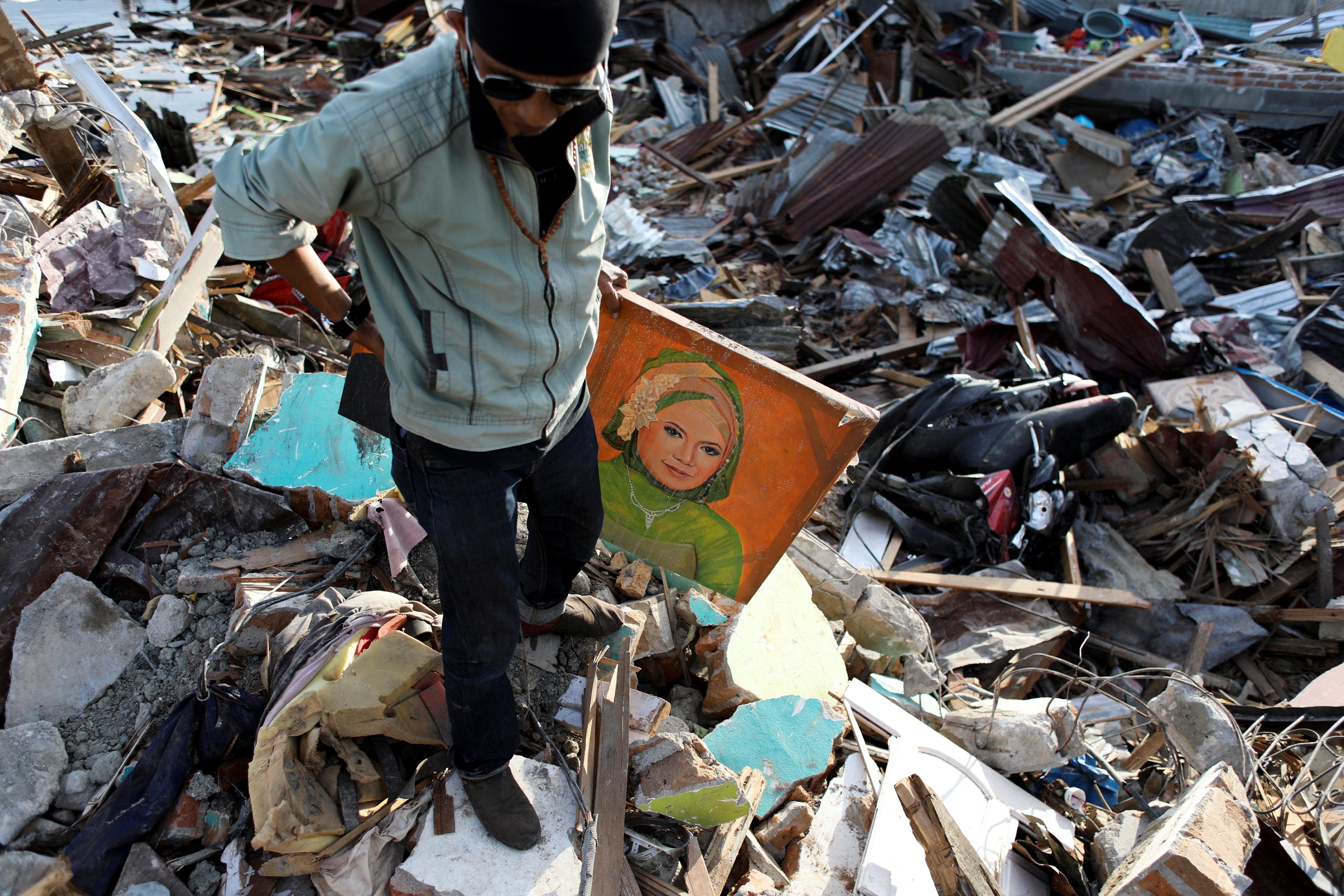 مواطن يحمل صورة أمه