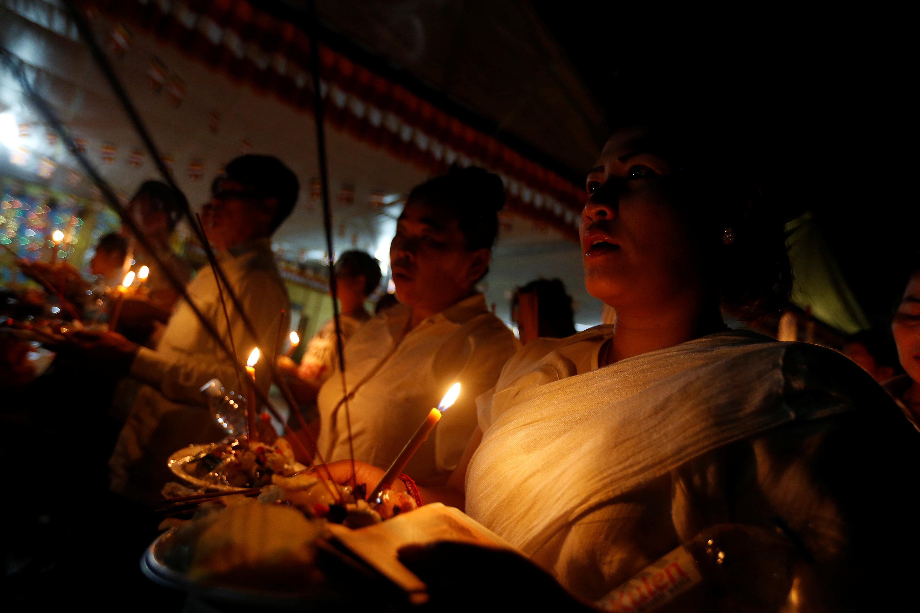 مواطنون يحملون الشموع لتأبين أرواح موتاهم