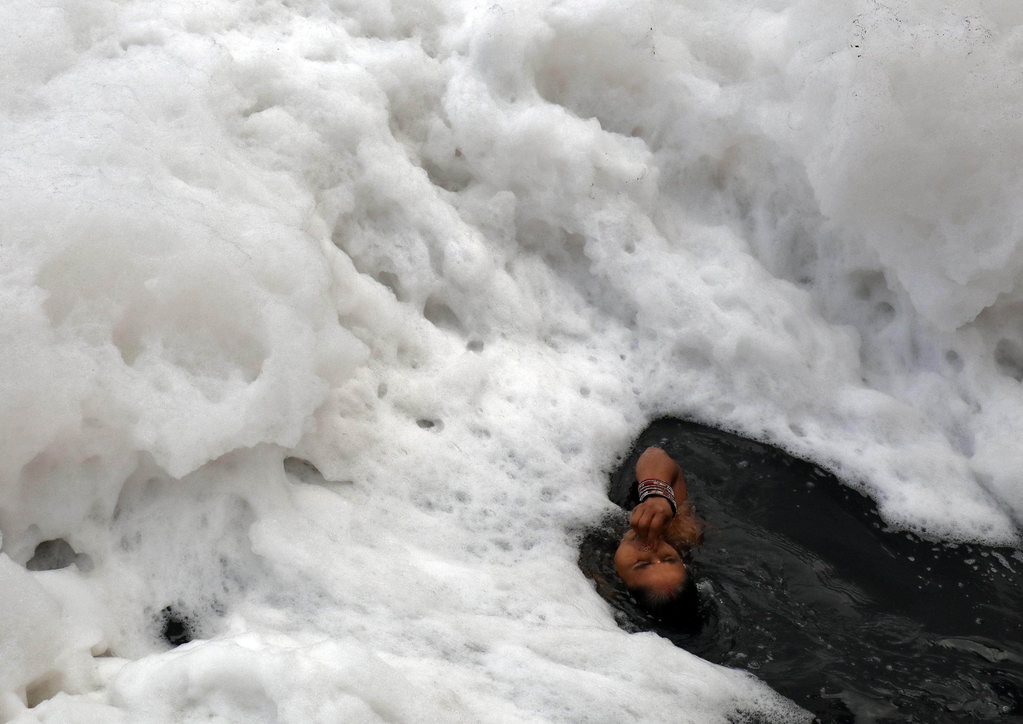 امرأة هندوسية فى مياه نهر يامانو خلال احتفالات عيد شاتا بوجا فى نيودلهى