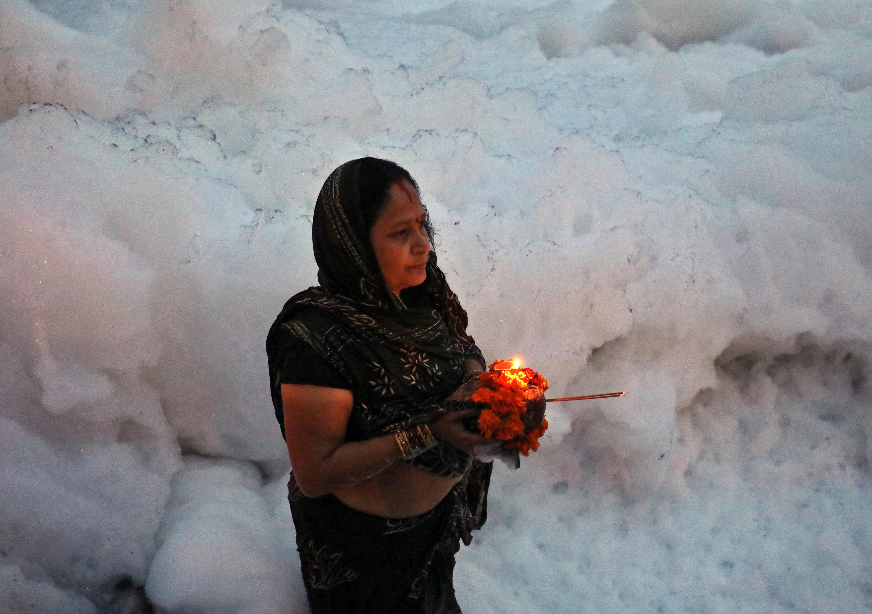 امرأة هندوسية من عبدة إله الشمس تحمل الشمع عند نهر يامانو