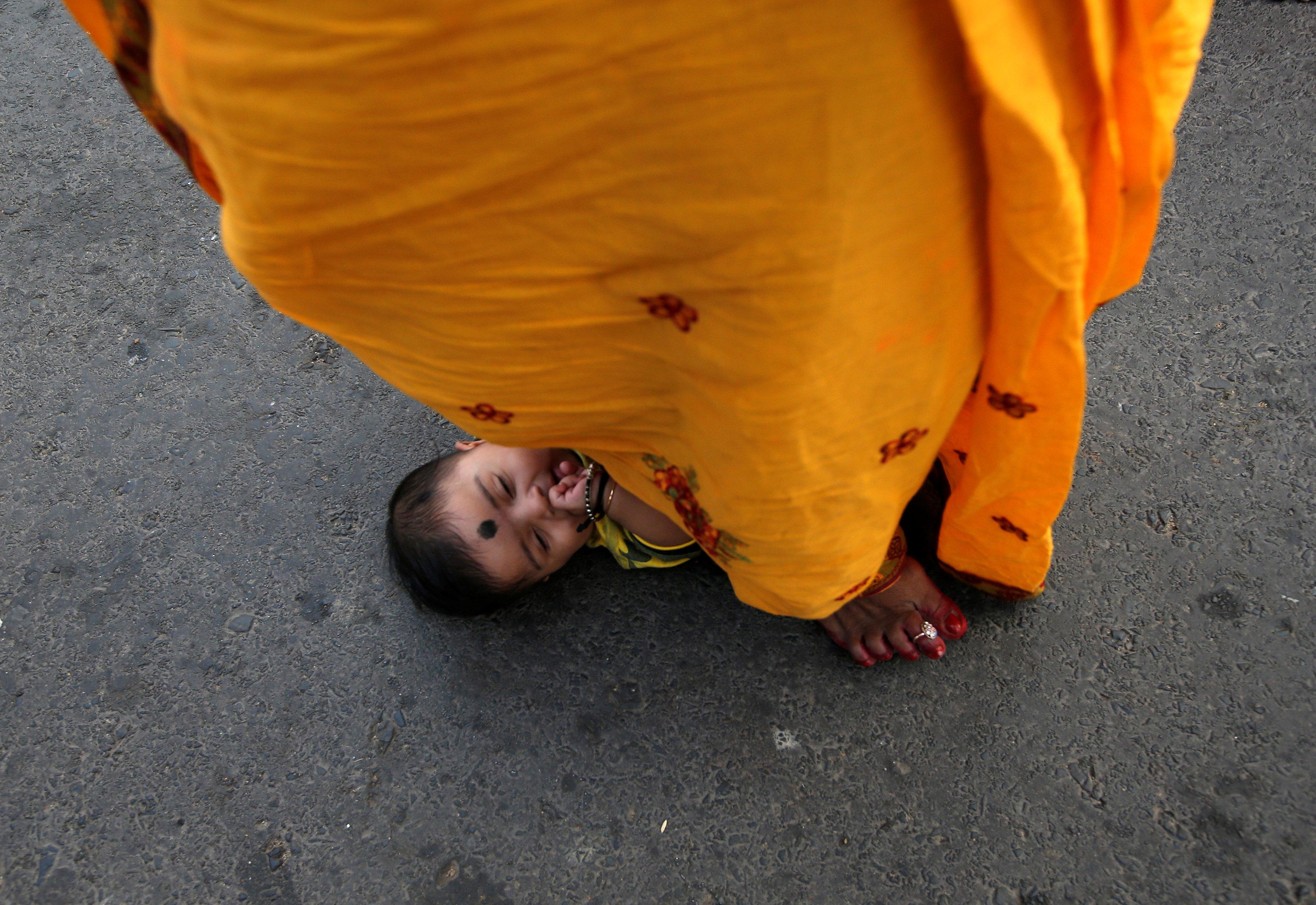 امرأة هندية تقف فوق طفل رضيع طلبا للبركة فى أحد طقوس العيد