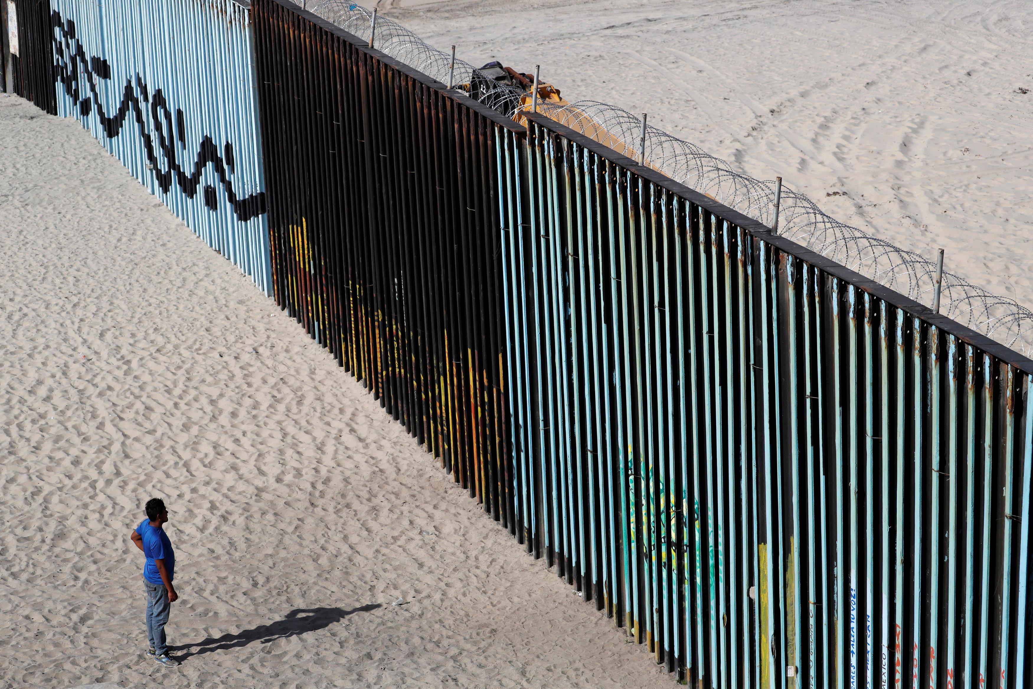 مواطن من أمريكا الوسطى أمام جدار المكسيك