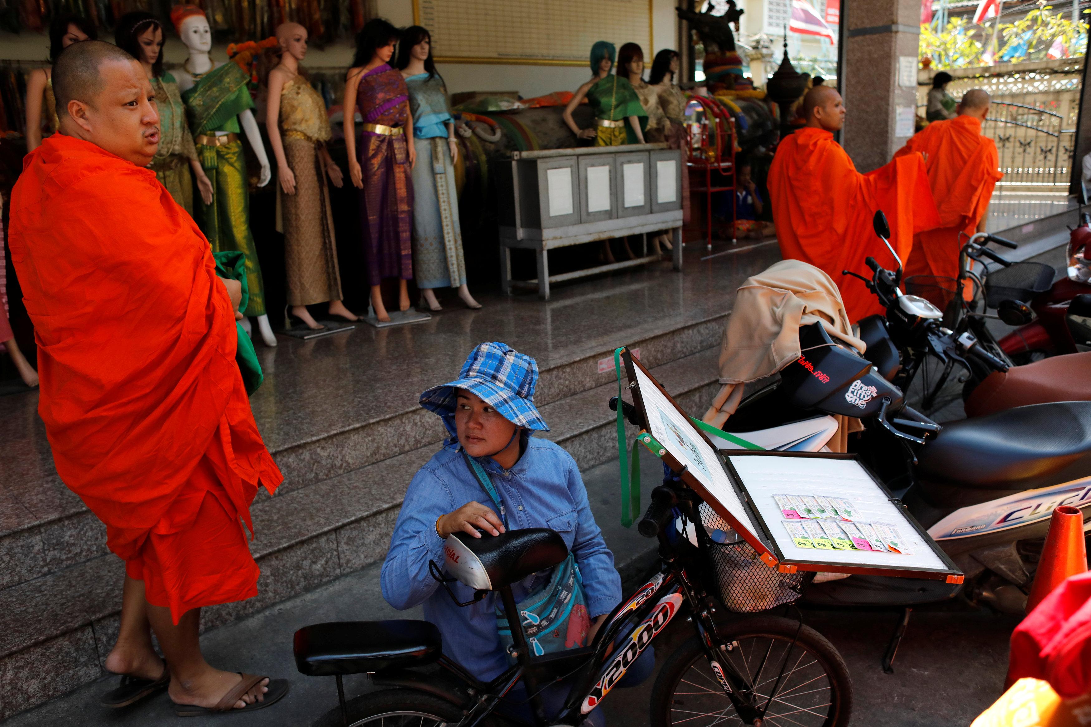 أحد بائعى تذاكر اليانصيب أمام أحد المعابد فى تايلاند